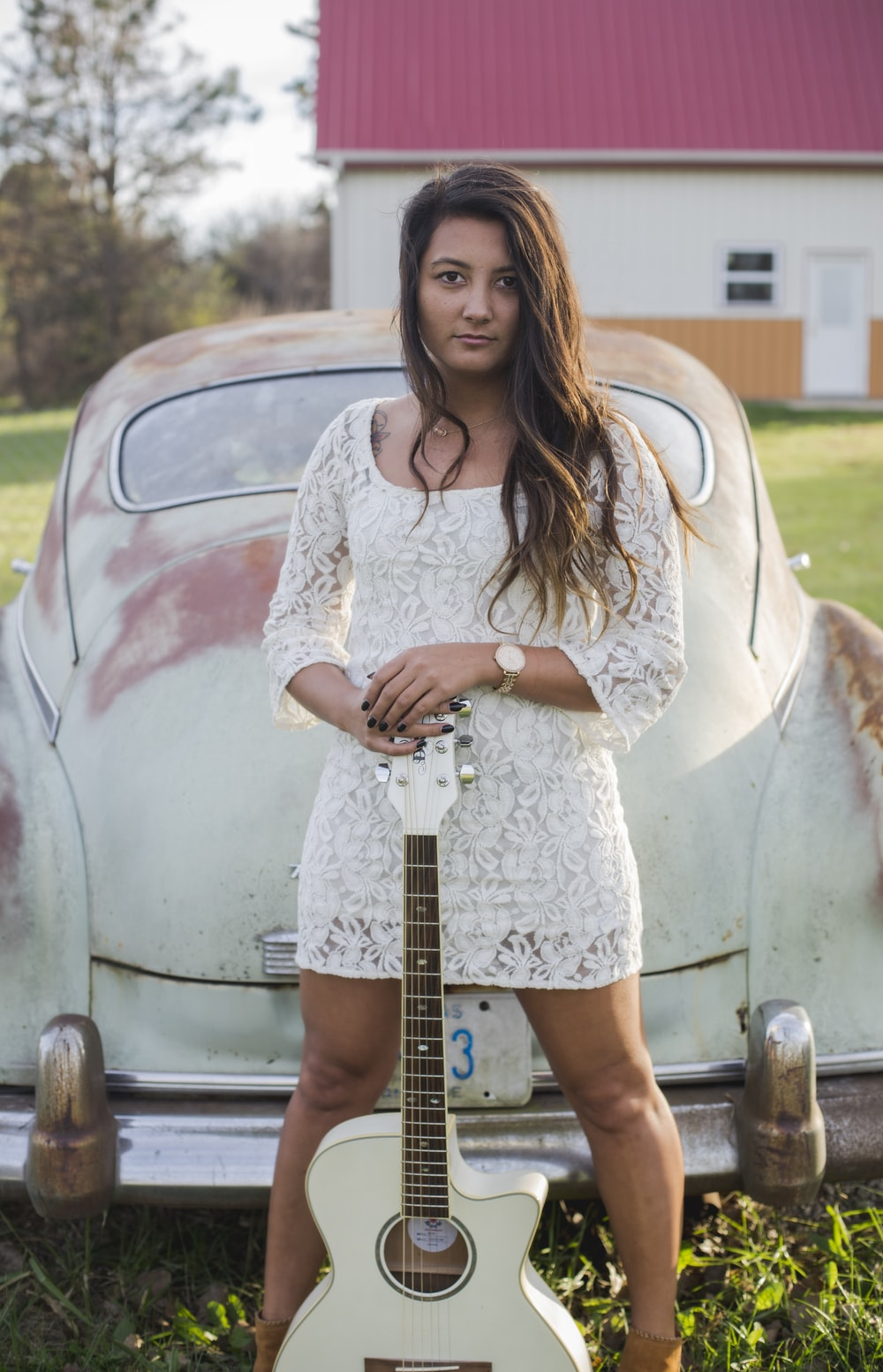 A woman in a dress holding a guitar in front of an older white car.