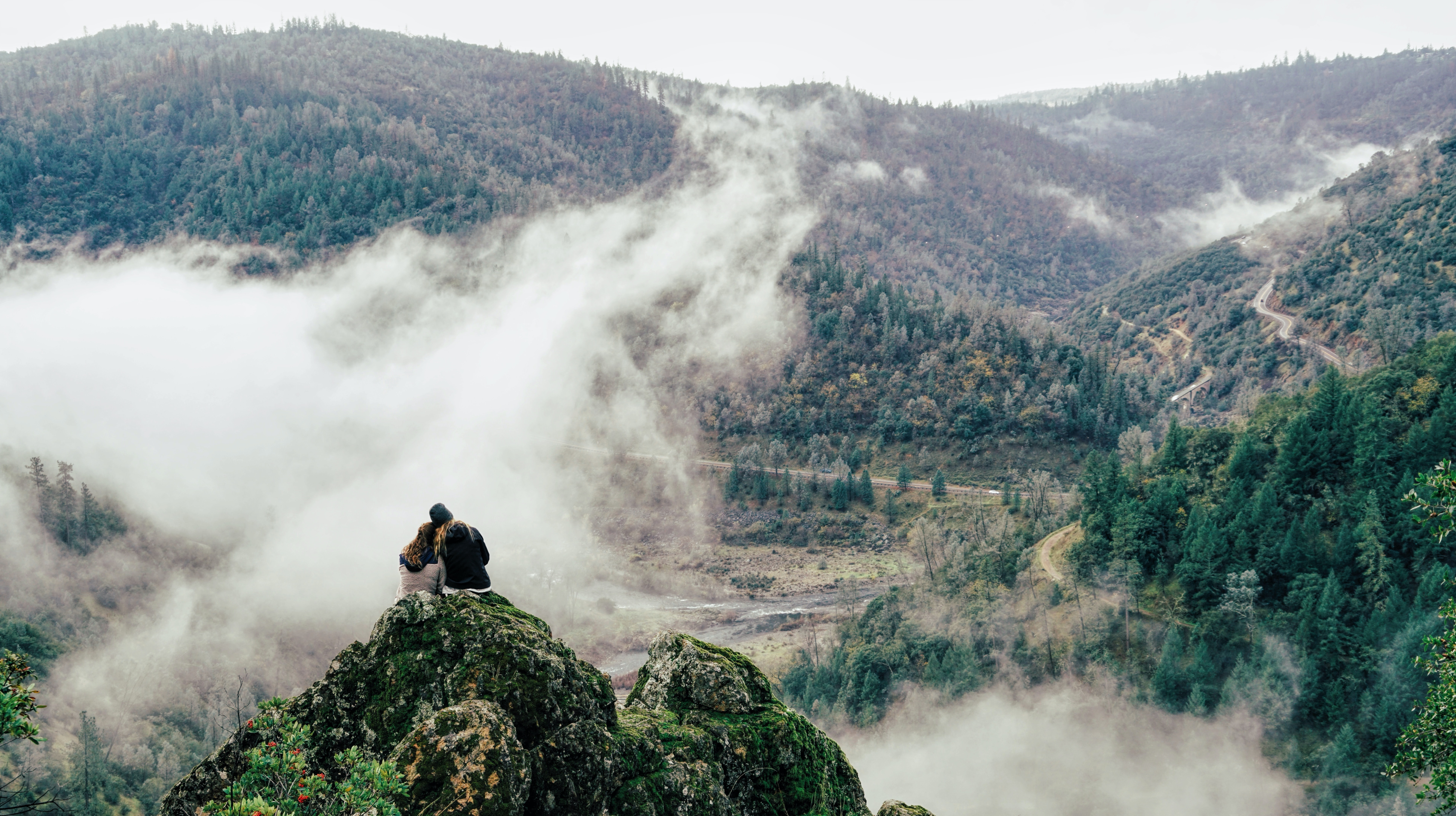 Two people leaning against each other on a moss-covered ledge in the mountains