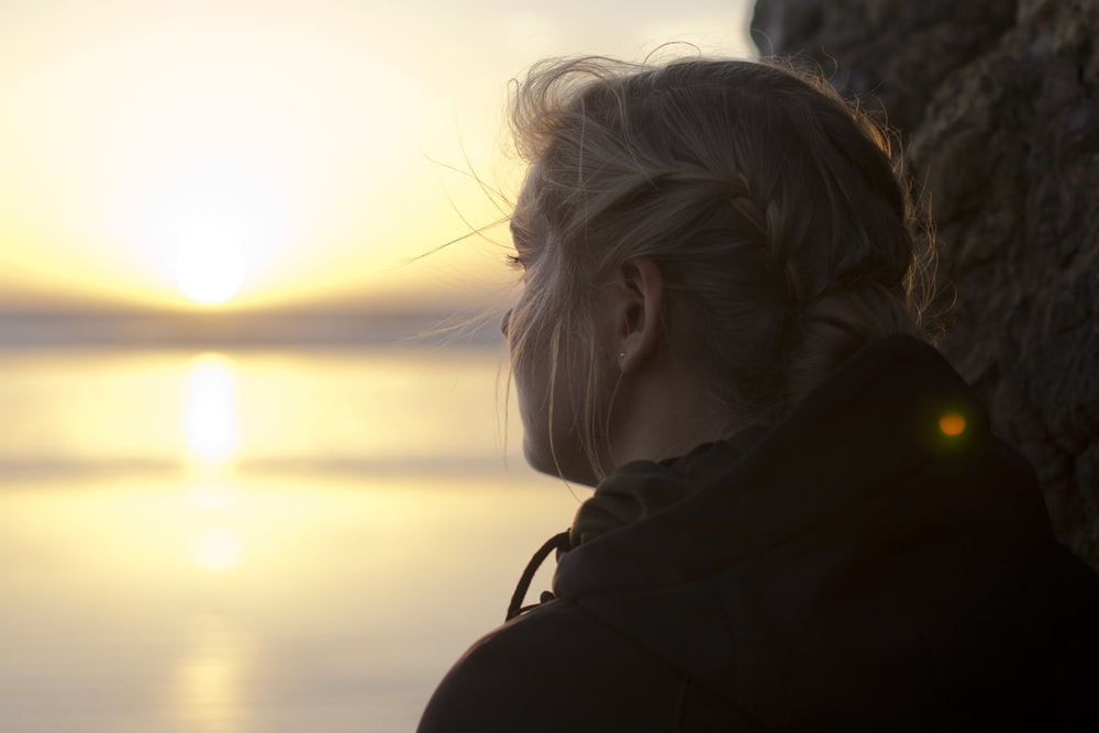 woman in black hoodie staring at the sea at sunset