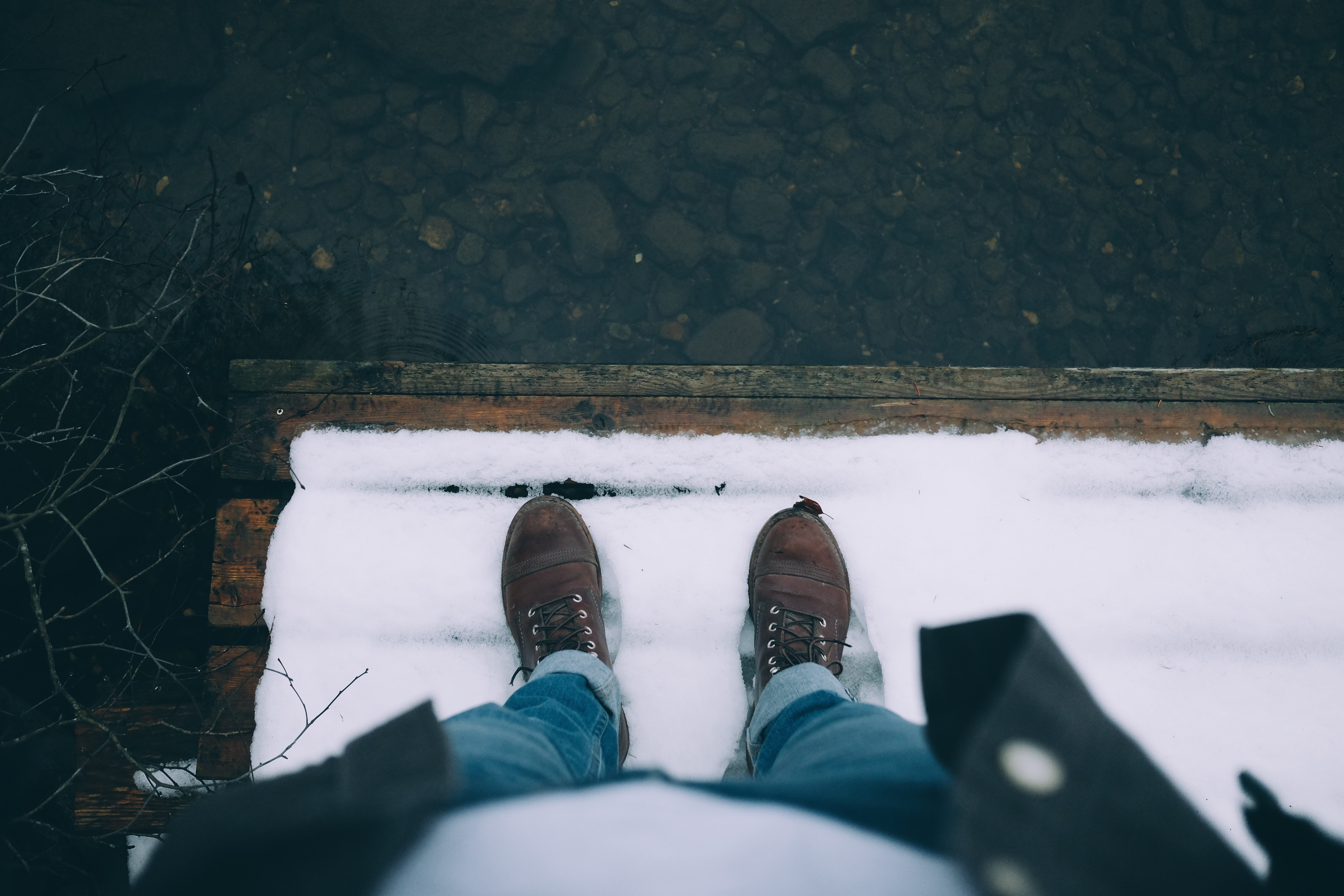 A person looking down at a pair of brown shoes in snow covered dock by the water.