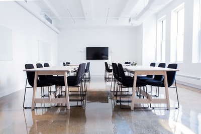a,boardroom,with,sever,tabl,and,a,televis,on,wall