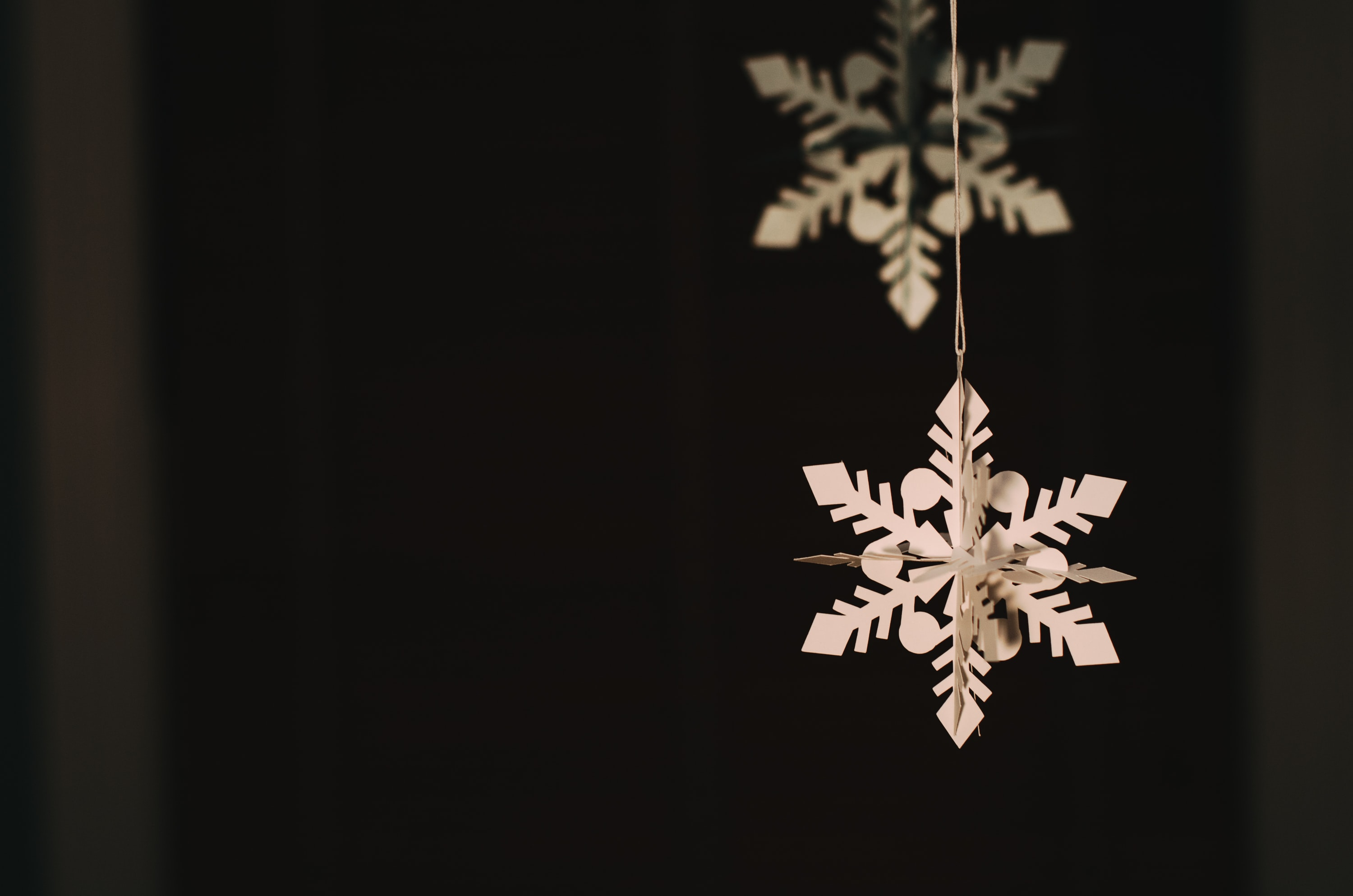 Macro of Christmas snowflake paper decorations hanging in front of black background, Brookline
