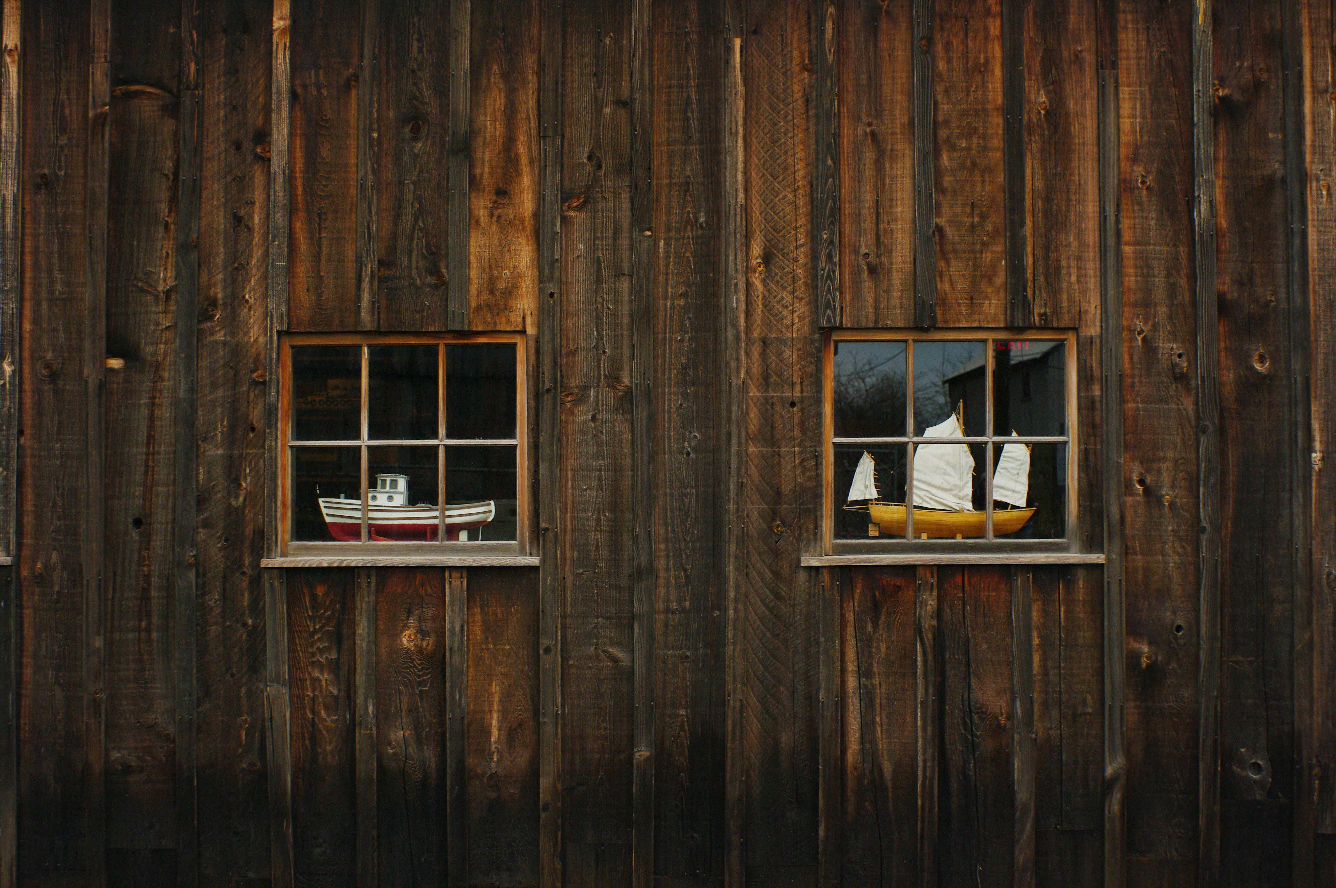 Wooden cabin wall with two windows in the side and sculptures of sailboats inside the cabin