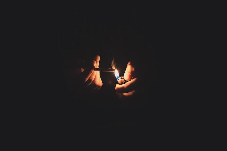 person lights a cigarette