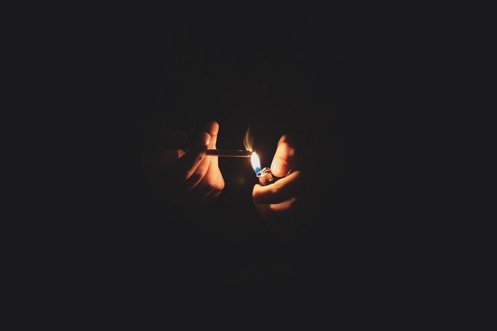 person lighting cigarette