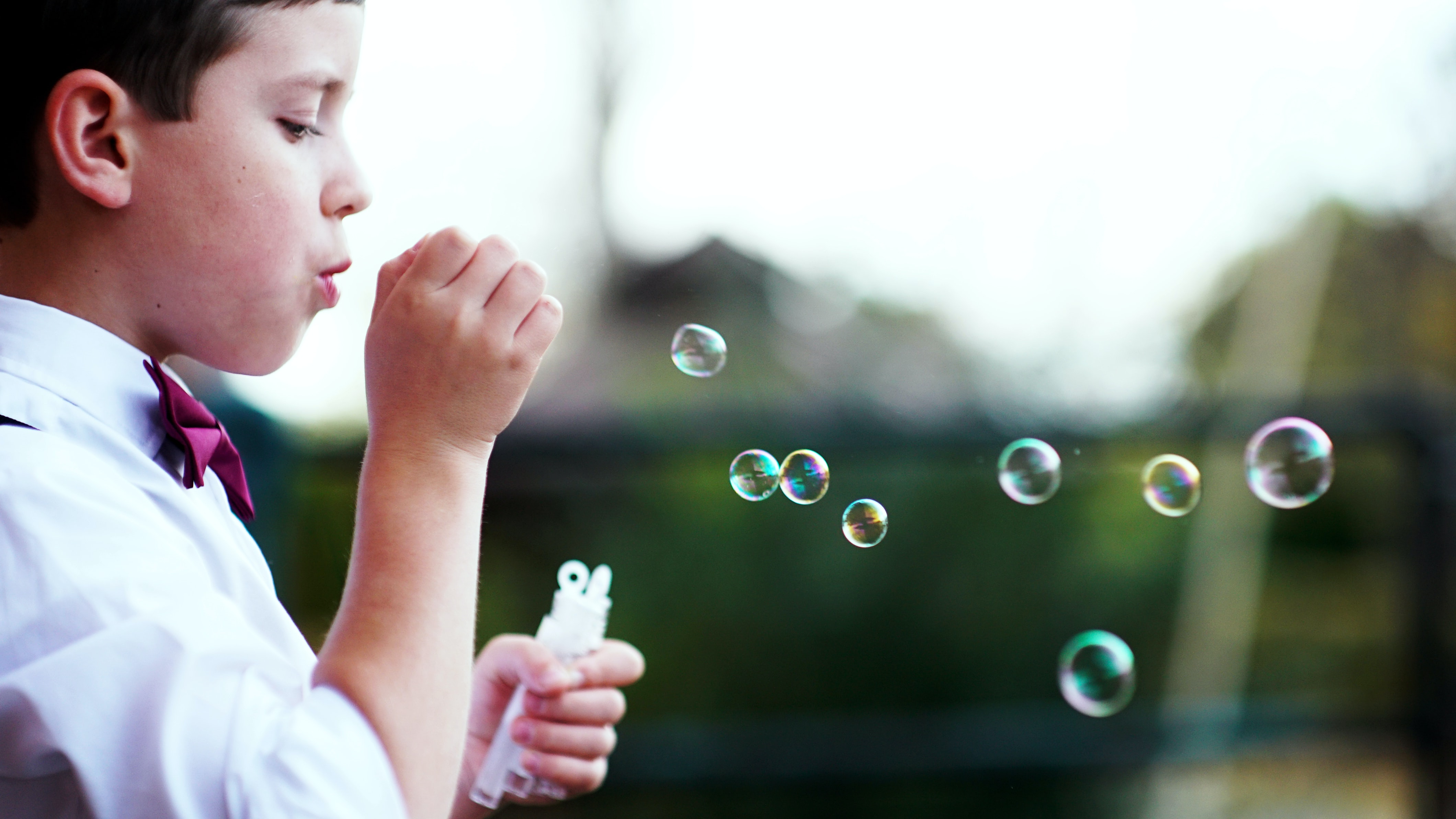 selective photography of boy playing with bubbles