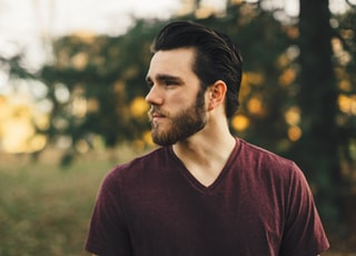man wearing maroon V-neck t-shirt in forest