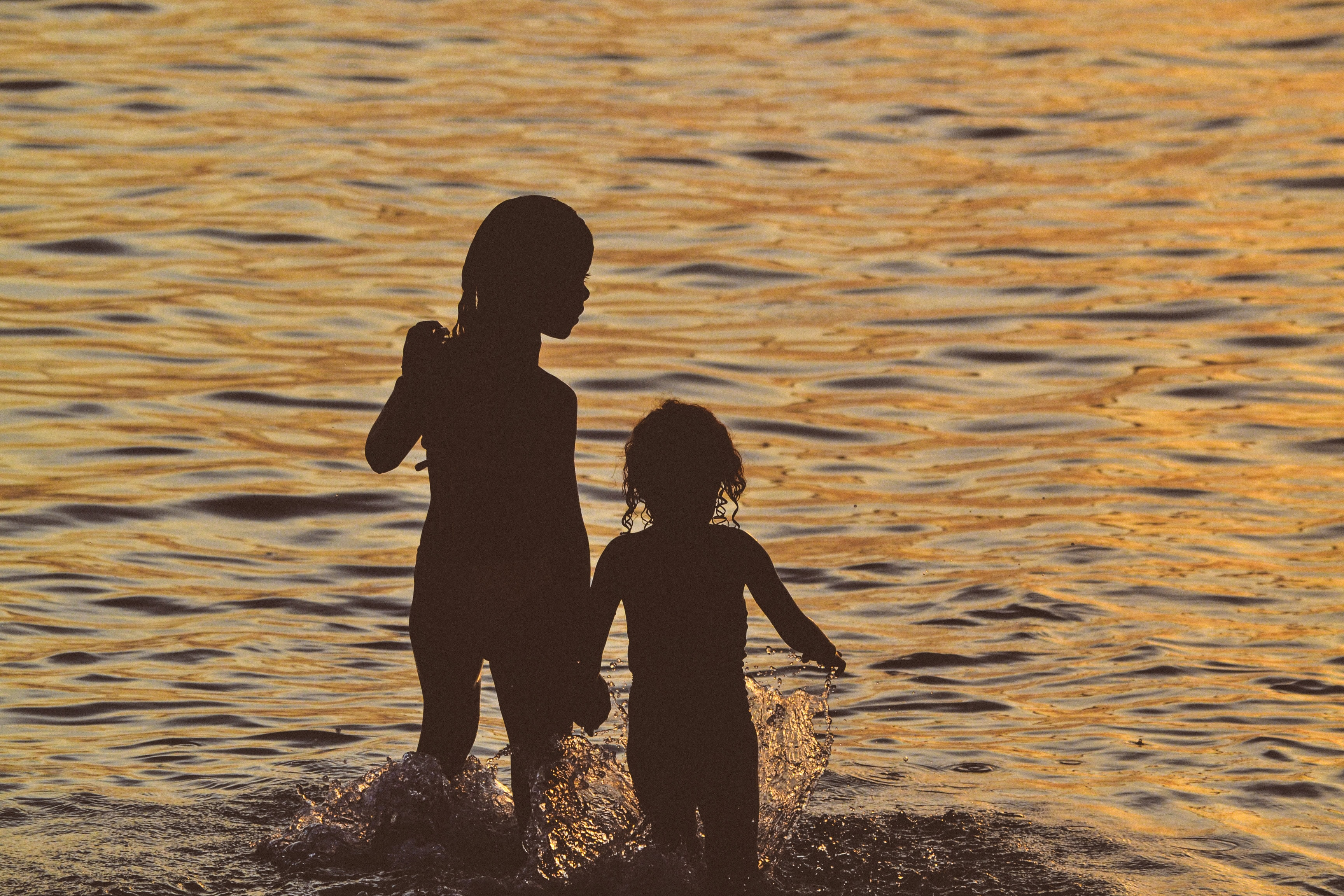 The silhouettes of two little kids splashing in the water at sunset