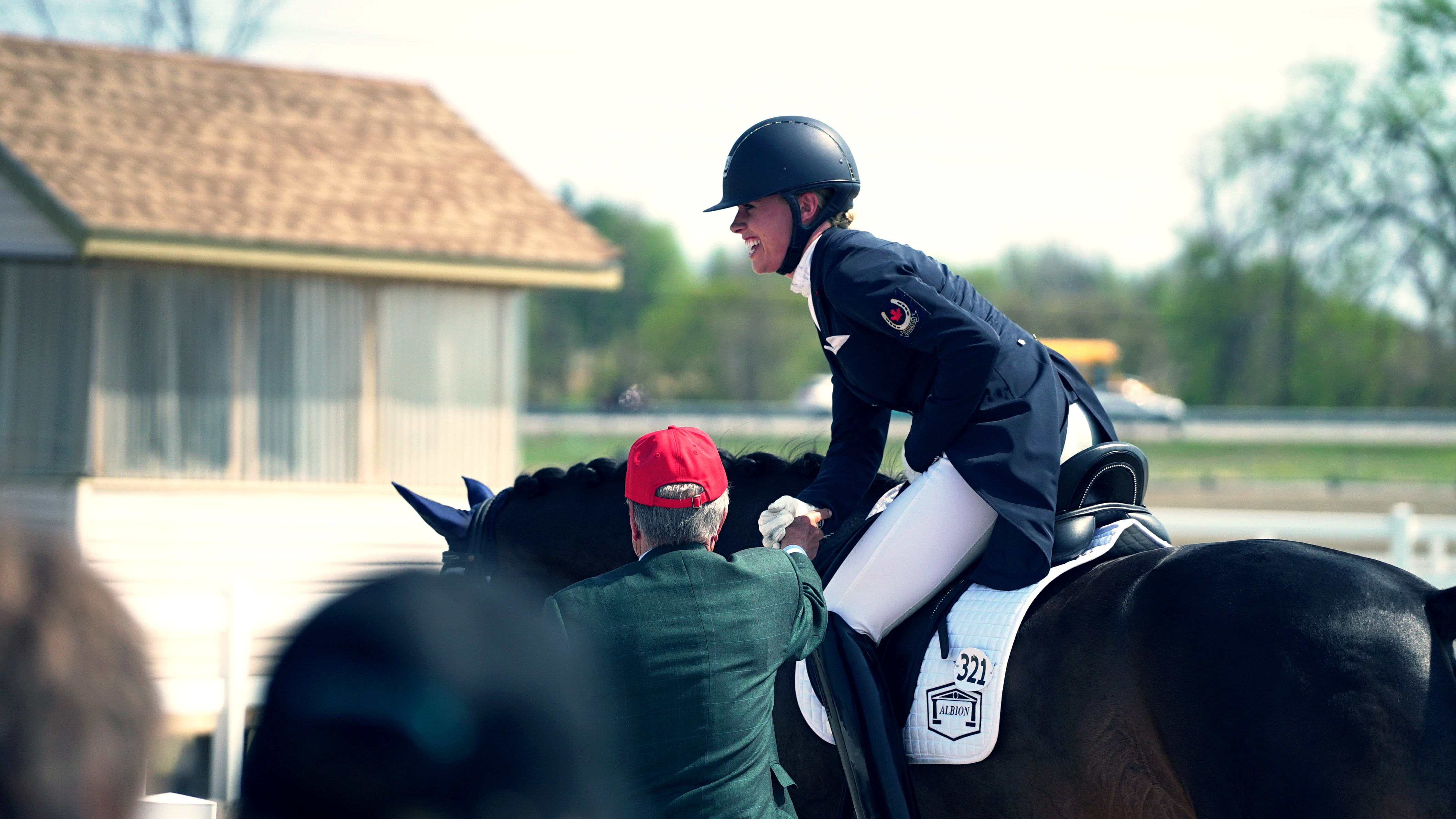 A woman equestrian rider sitting on her horse, talking to her coach in Ottawa