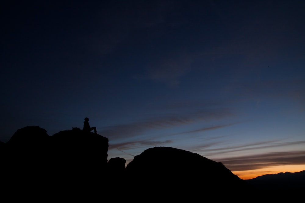silhouette of person sitting during sunset