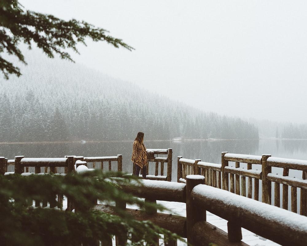 woman walking towards brown wooden bridge
