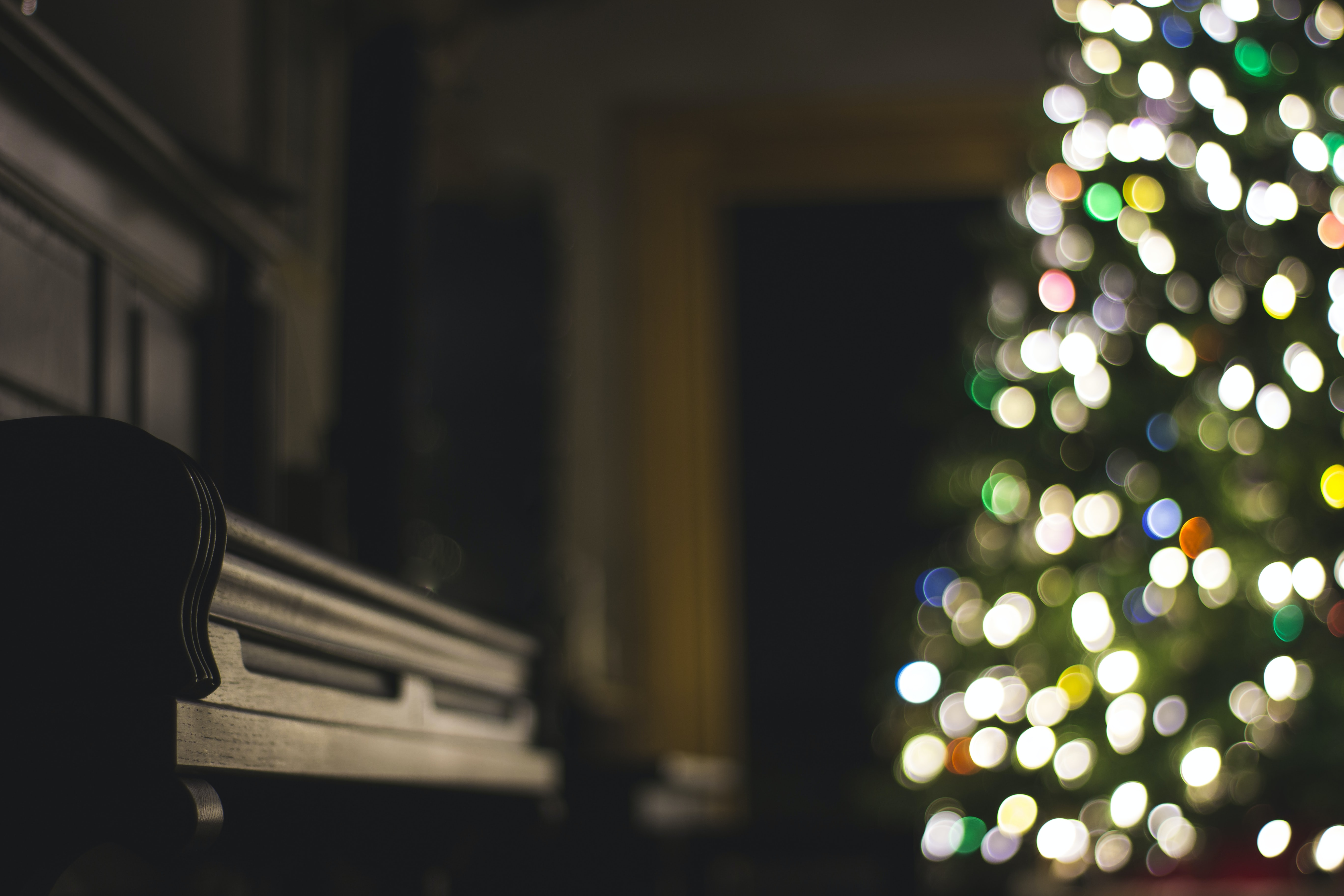 A dim shot of a piano next to a Christmas tree with bokeh effect
