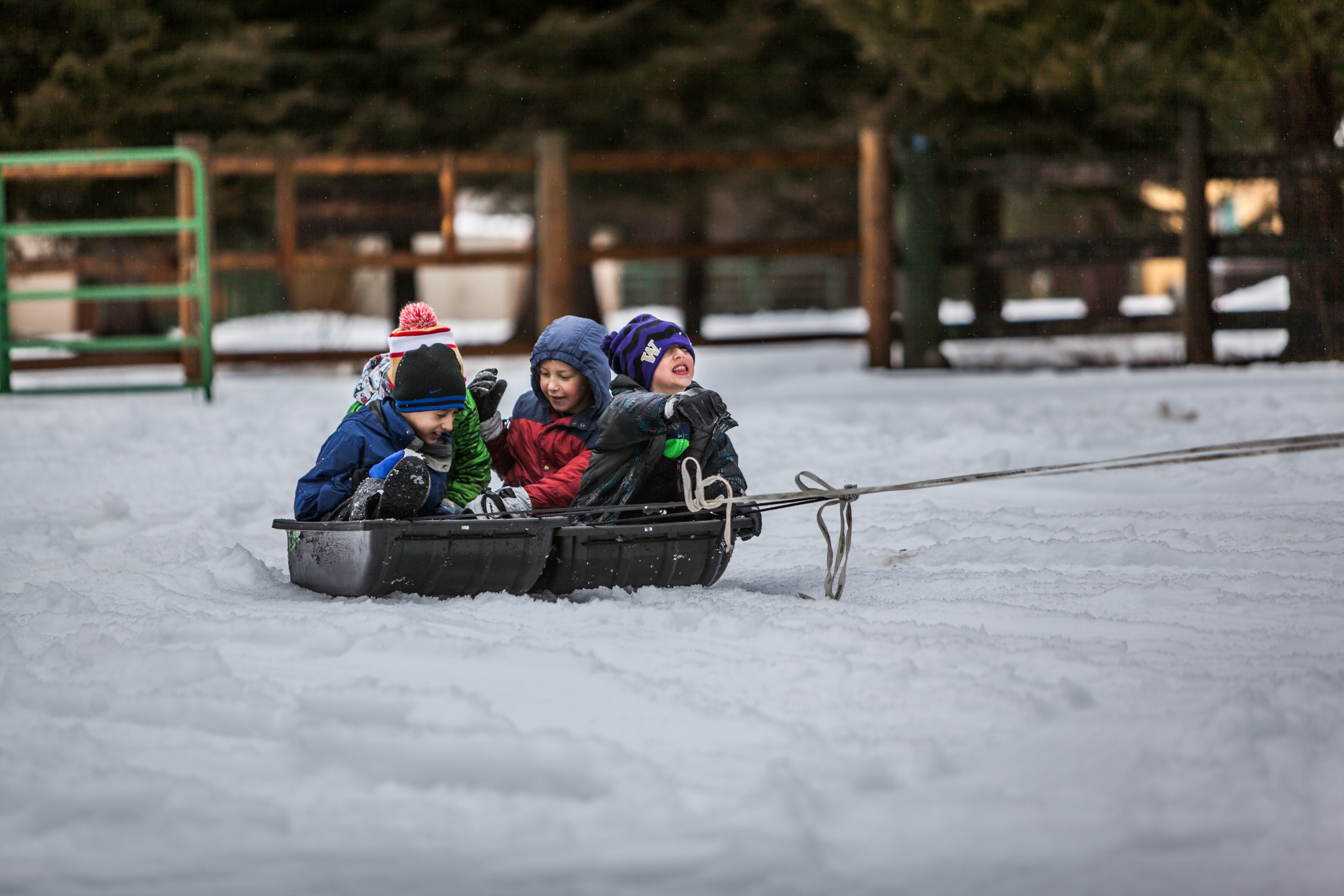 Children riding on a sled pulled by a rope in a fenced area in the cold