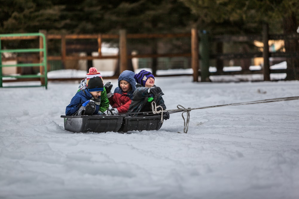 four children riding boat on snow