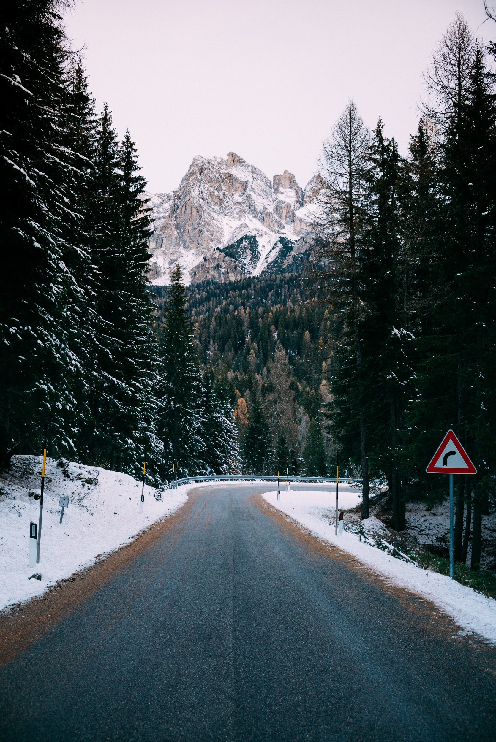 A curve in an empty road on a snowy day in the Dolomites