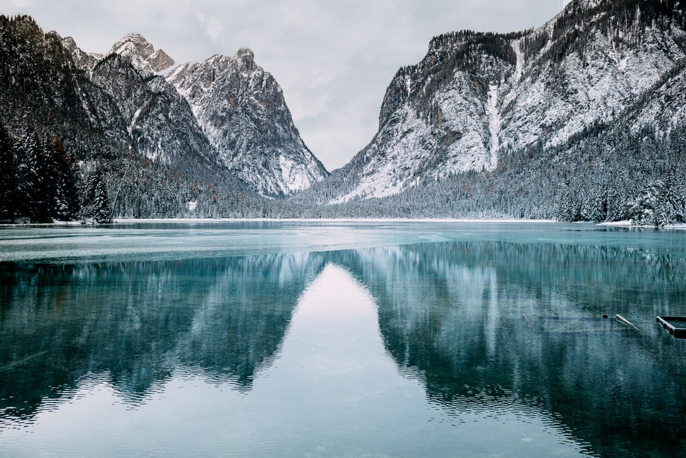 body of water and snow-covered mountains during daytime