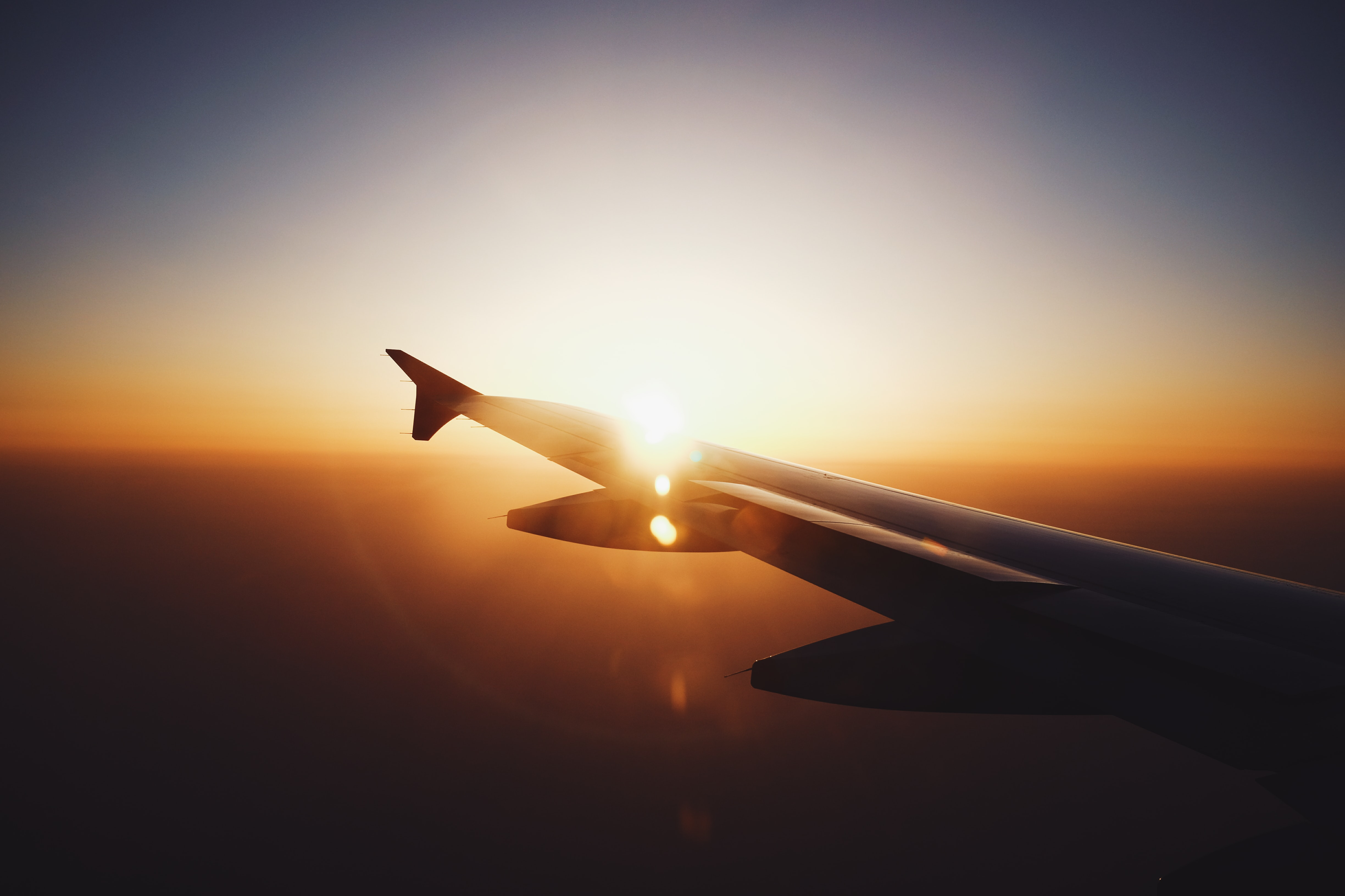 Silhouette of an airplane wing in flight, against the sun setting, with lens flare and vignette effects