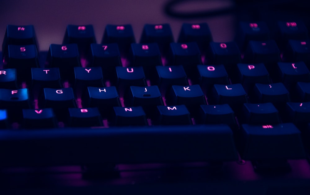 focus photography of computer keyboard with red lights