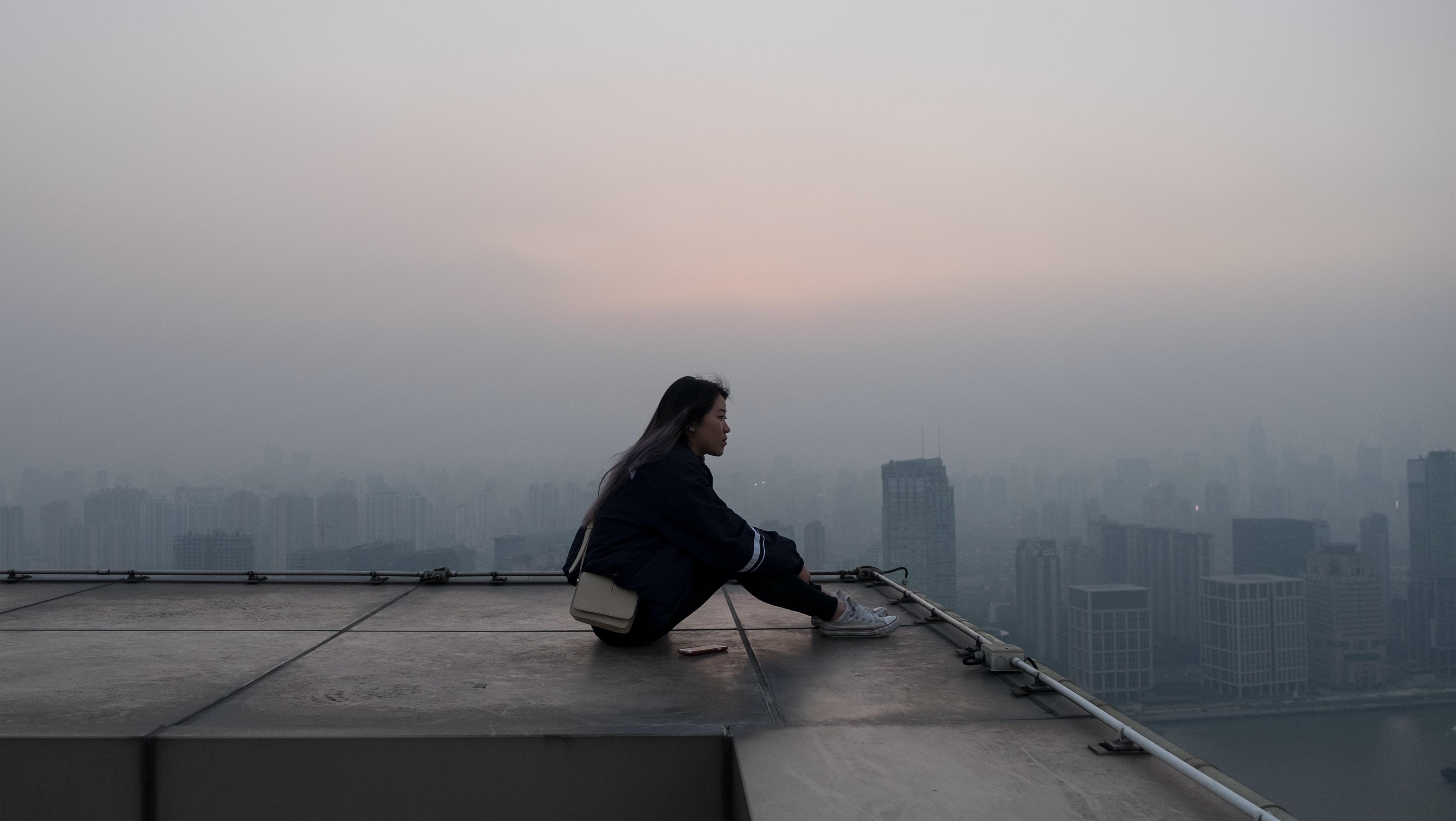 woman seating on skyscraper