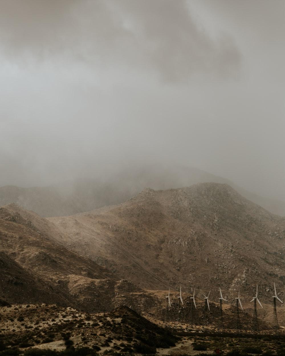 white wind turbines beside mountain