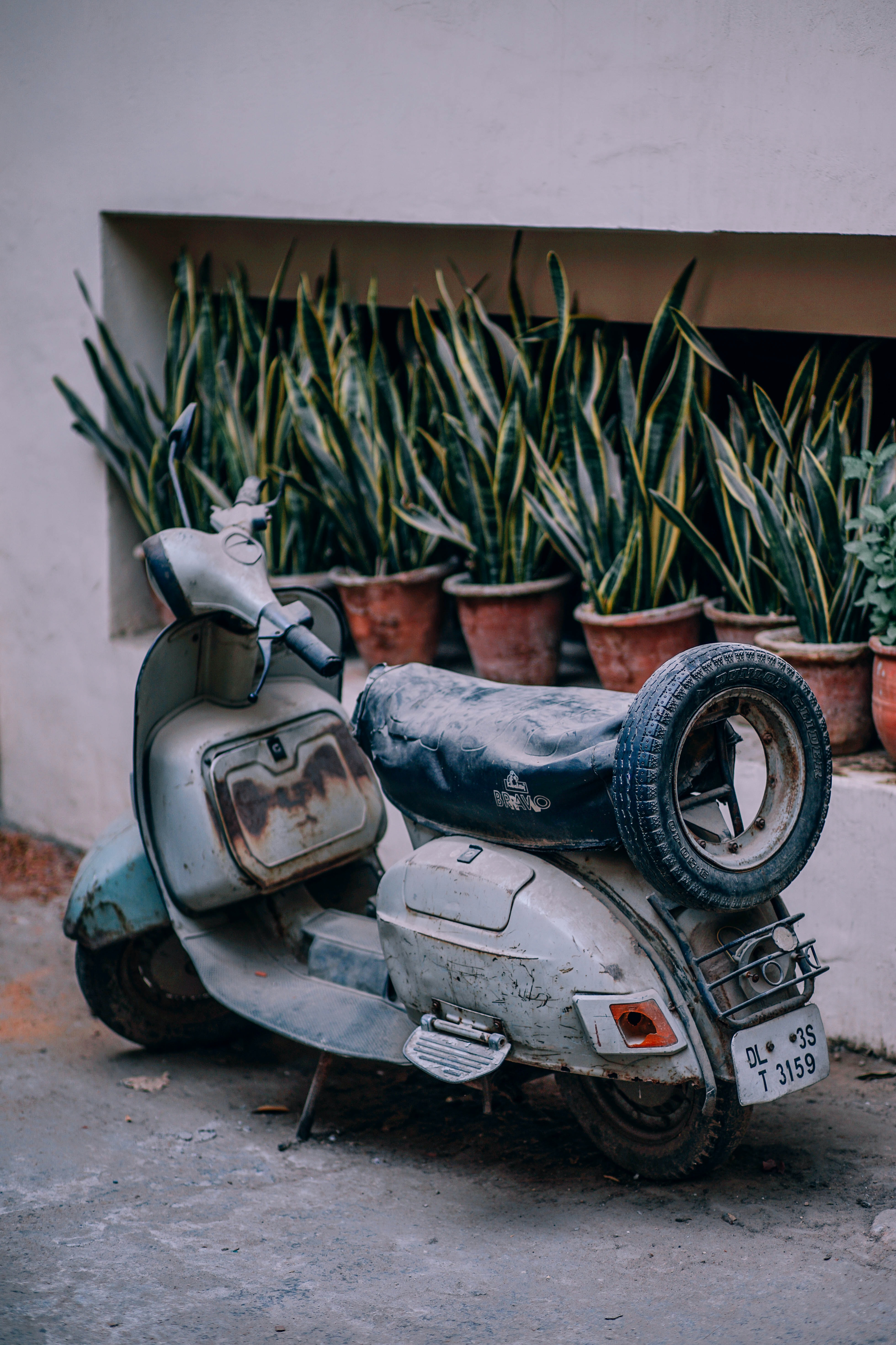 An old moped parked in the driveway.