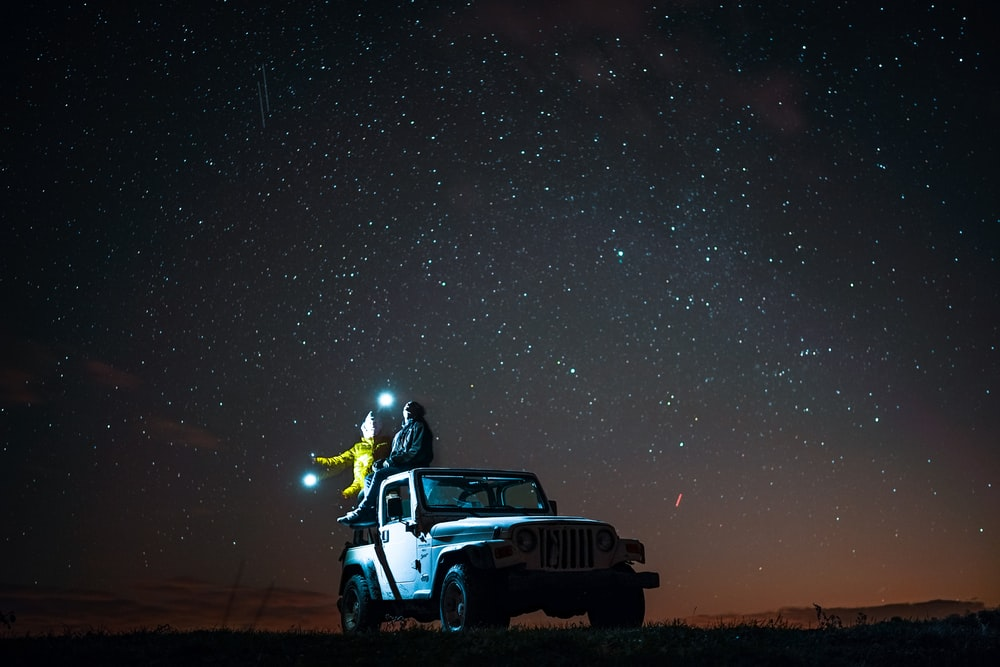 person sitting on top of wrangler under starry sky