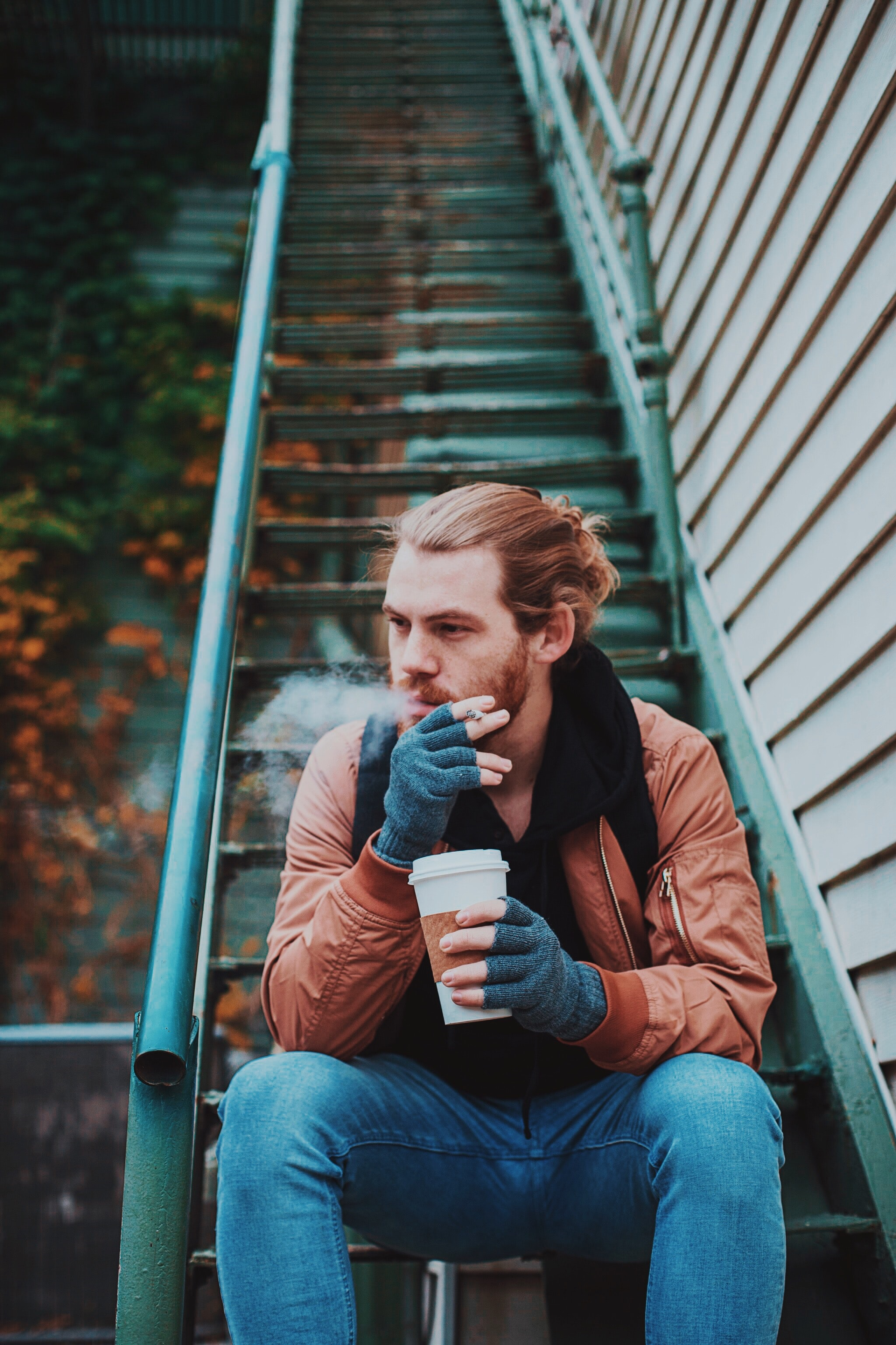Hipster man with a man bun drinking coffee on a staircase