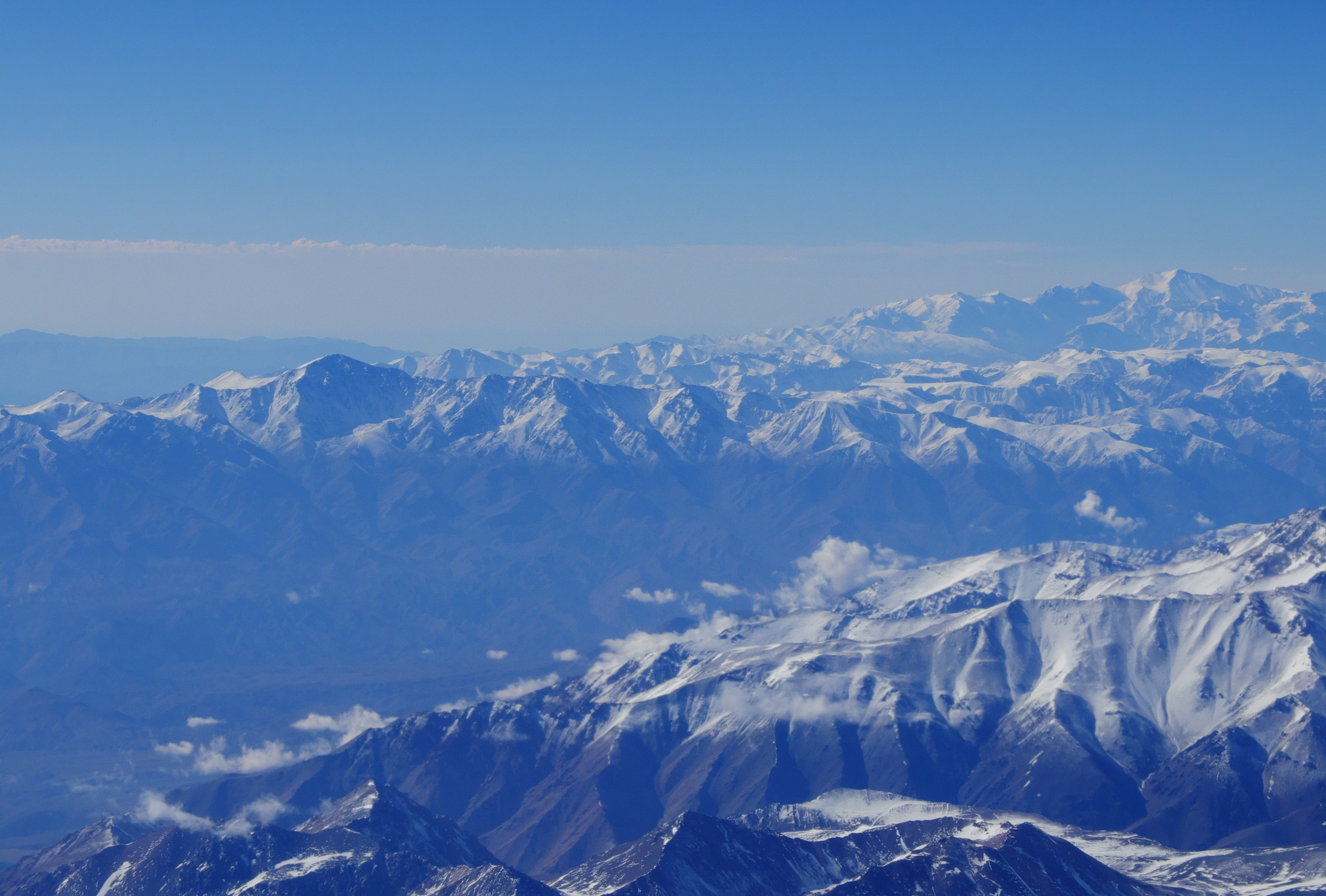 A blue-hued shot of long mountain ridges in the Andes