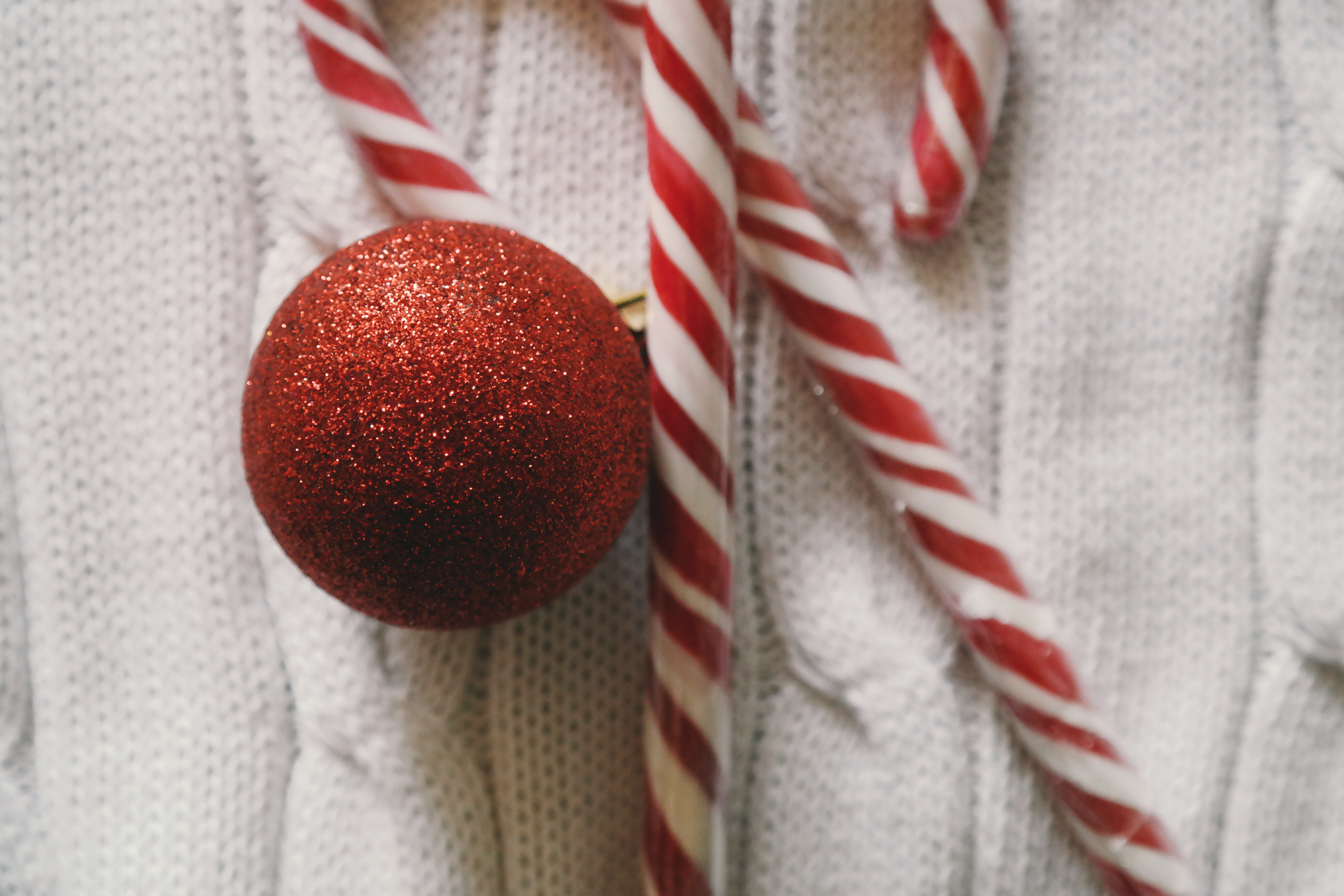 Two candy canes and a red XMAS ornament.