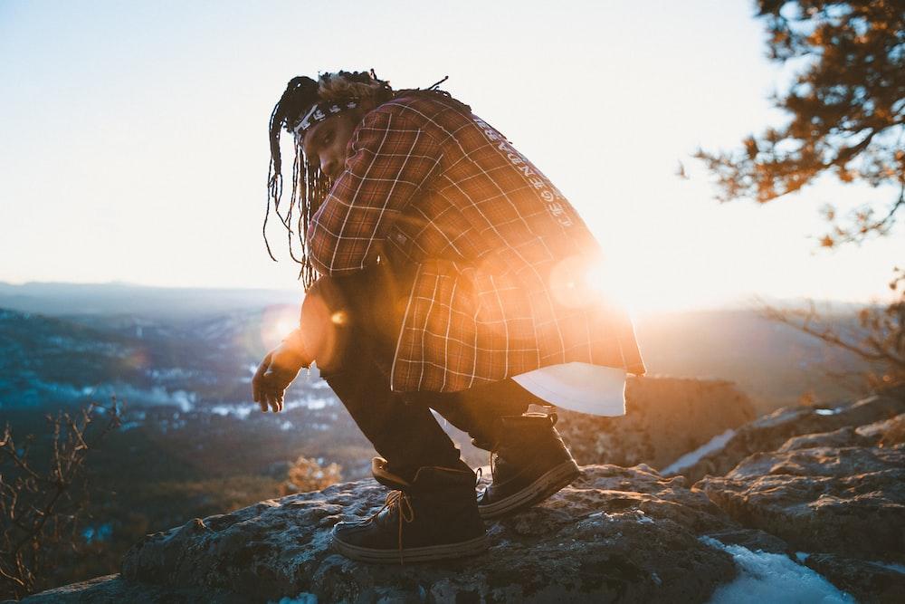 man sitting on rock near cliff