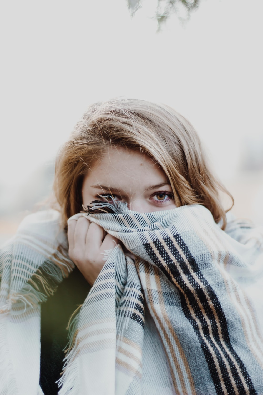 woman hiding her face with scarf
