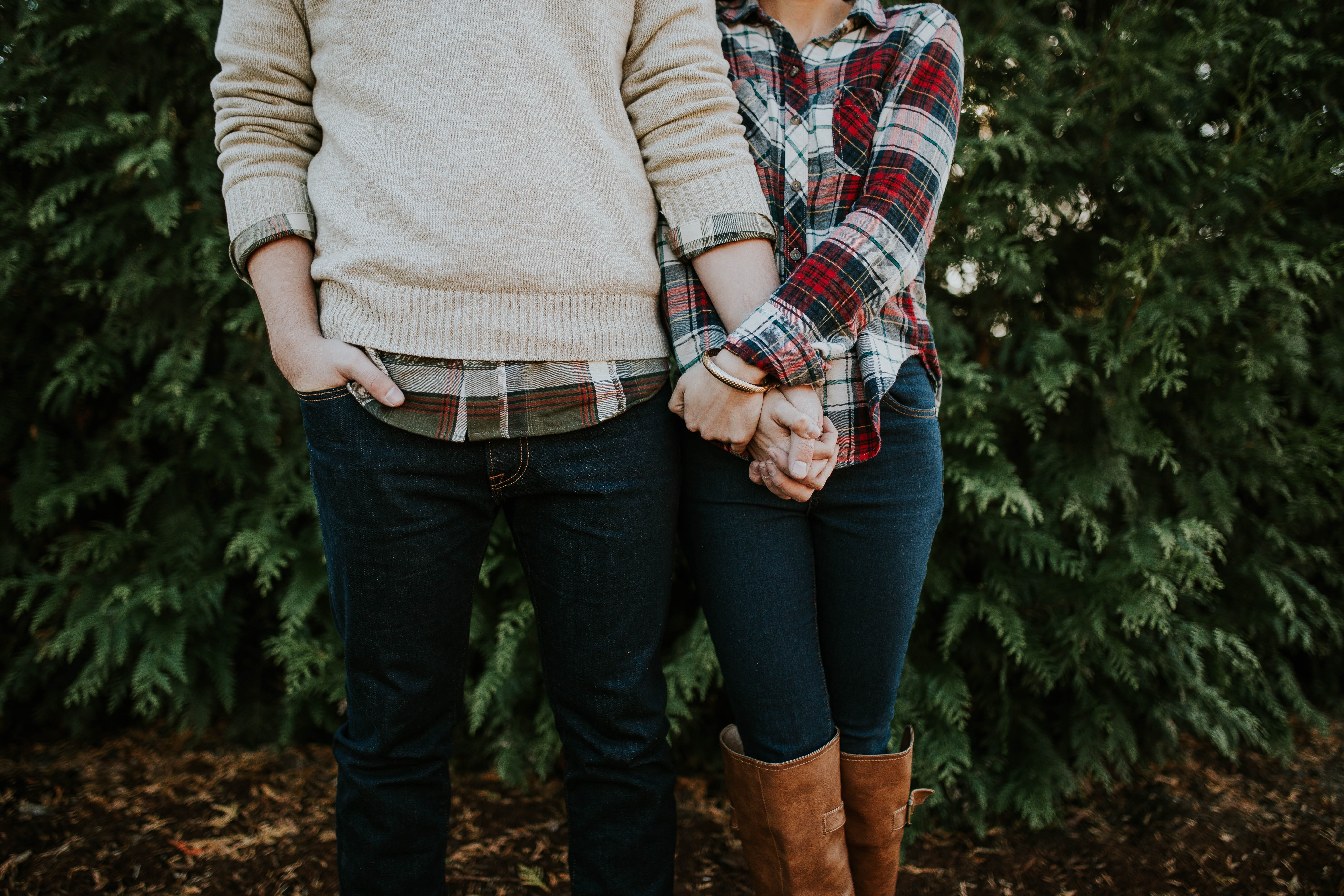 Couple in plaid, jeans, and sweater holding hands at Botanical Garden of the Ozarks