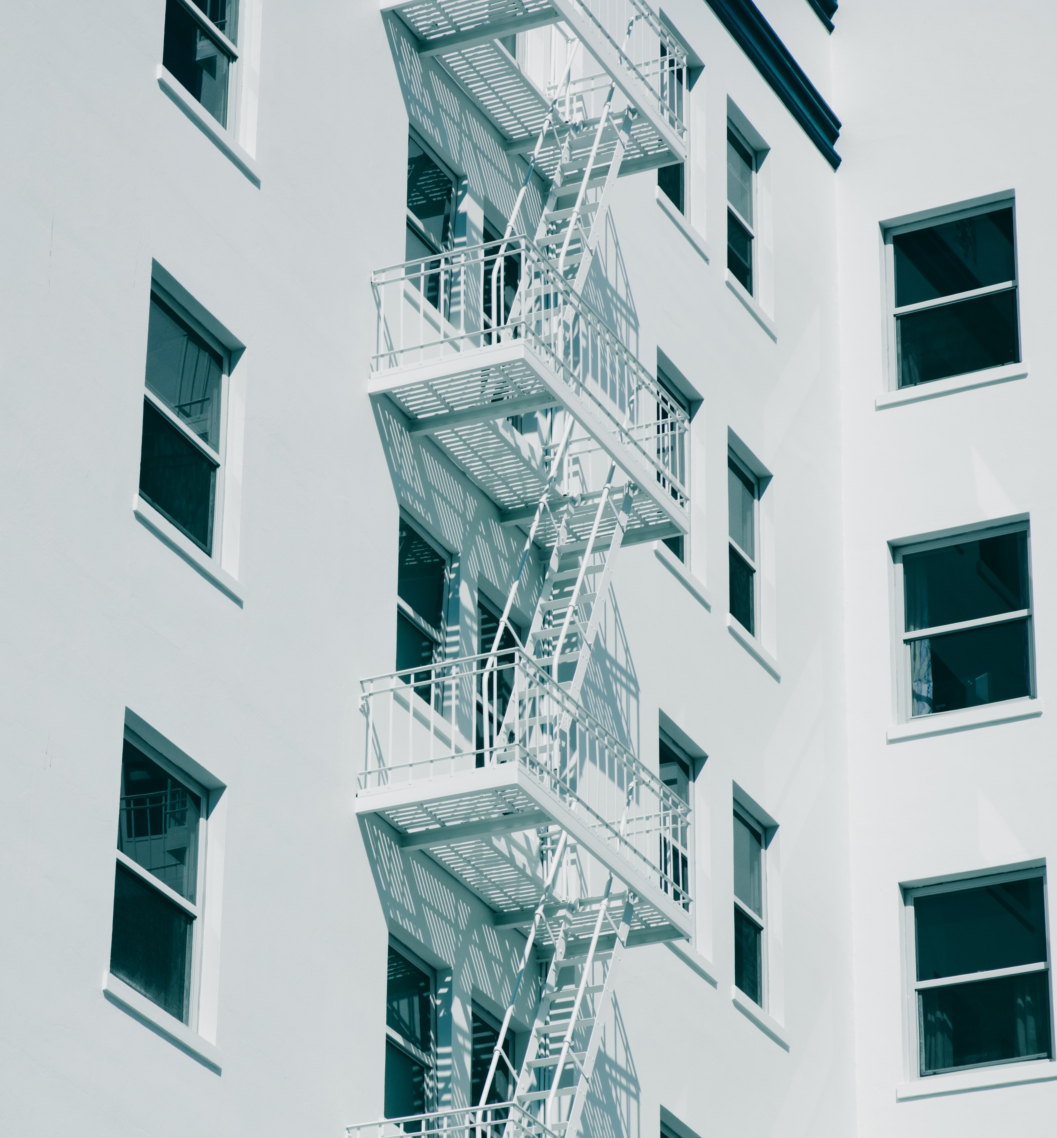 Black and white shot of white fire escape staircase and windows on building in Berkeley