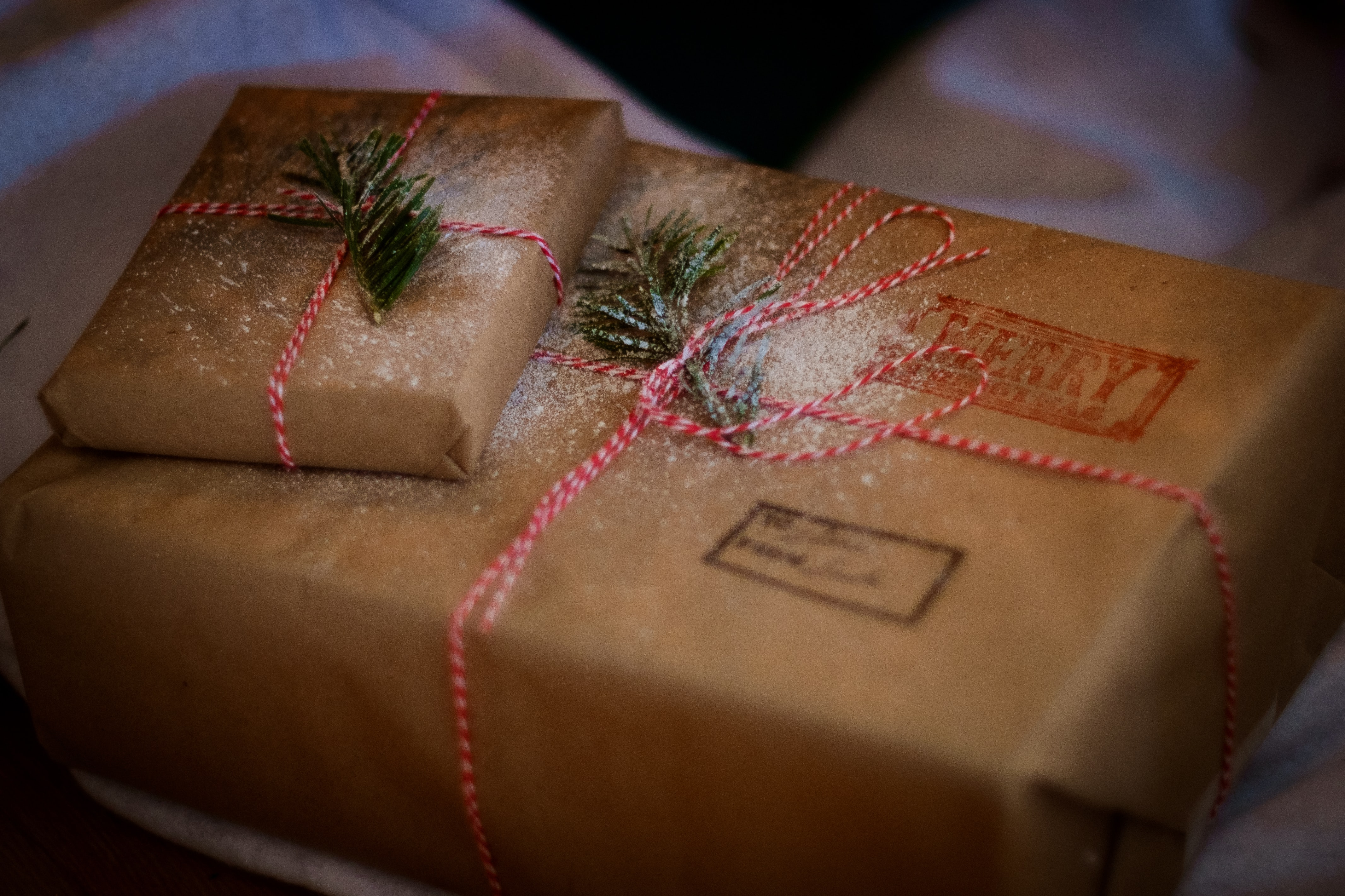 Christmas gift parcels wrapped in brown paper and decorated with twine and pine leaves.