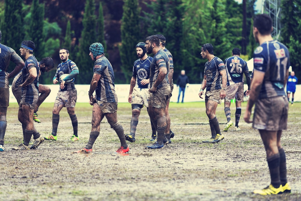 soccer players standing on muddy field