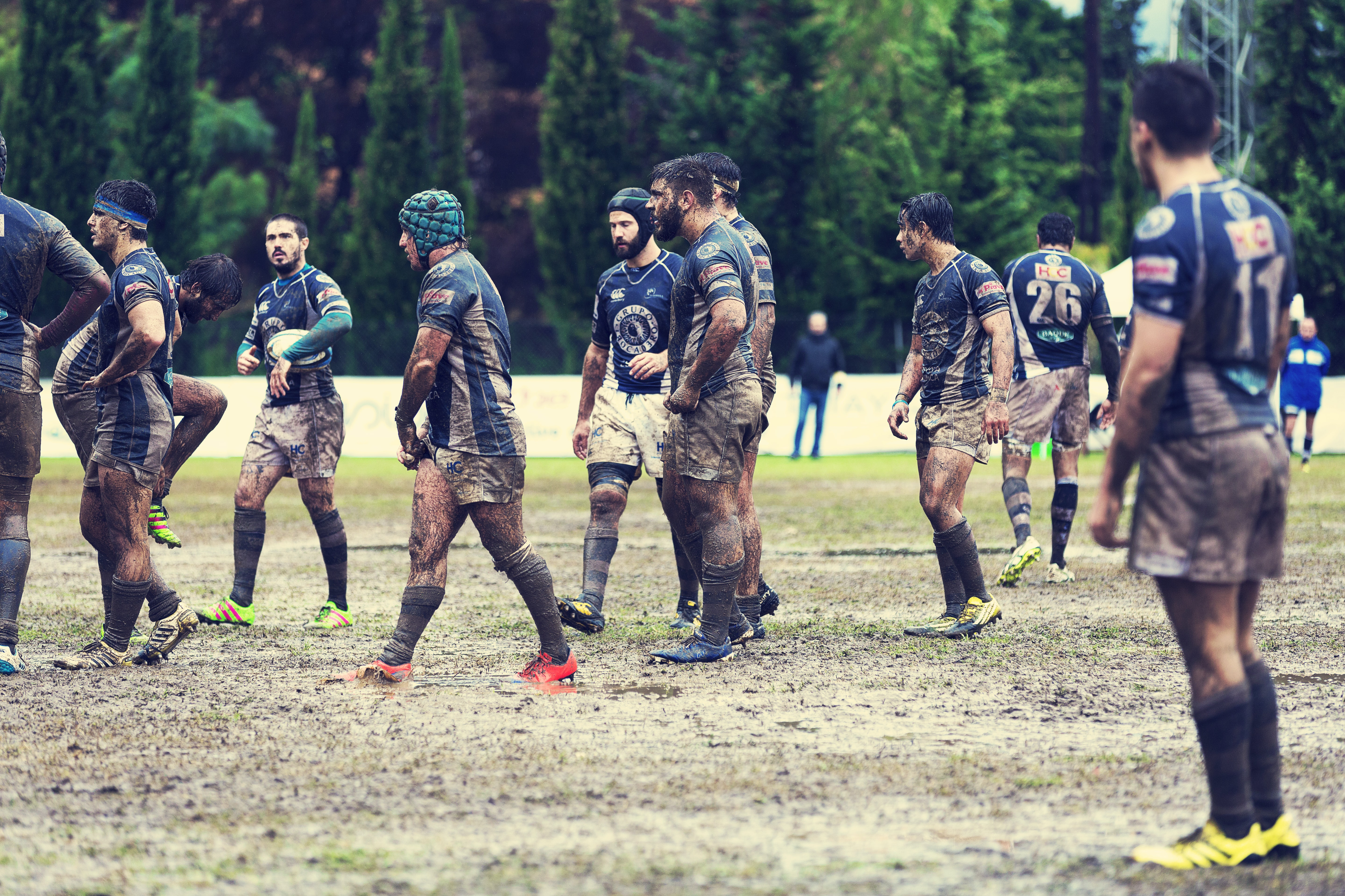 A male rugby team covered in dirt and mud on a field during a game