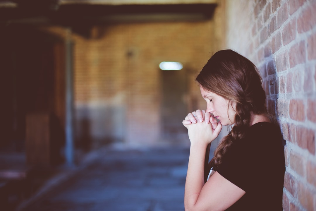 A woman wearing a braid in her hair is leaning against a brick wall, praying