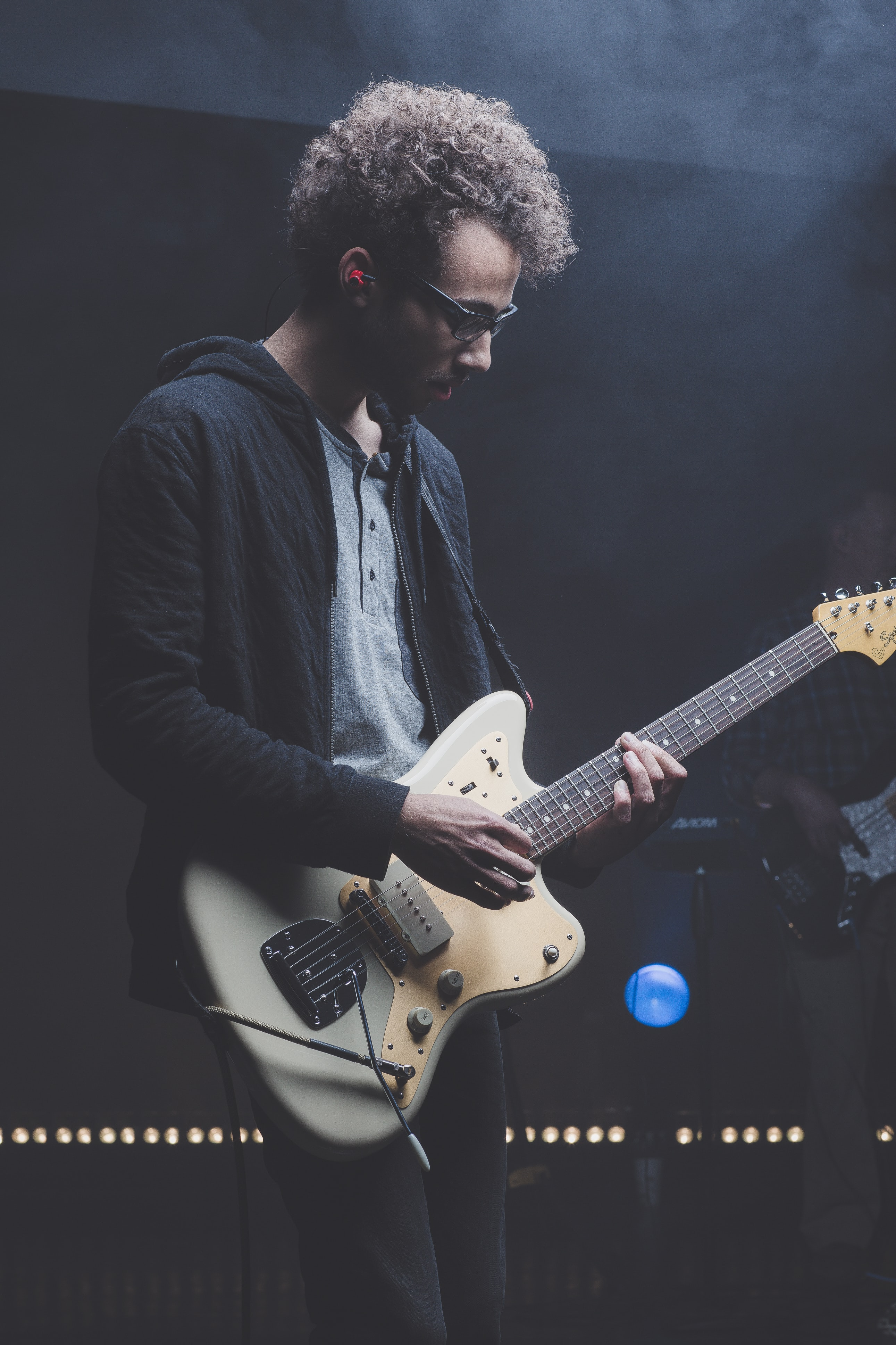 A young man in glasses playing electric guitar on stage in Colorado Springs