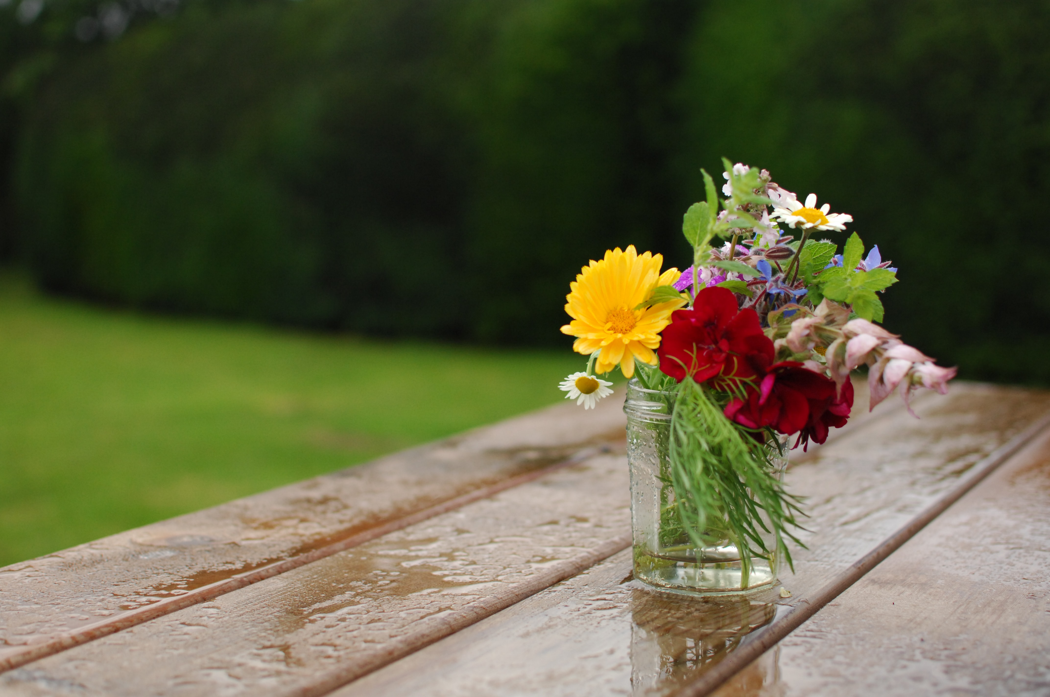 A small vase with various types of colorful flowers on a wet wooden surface outdoors