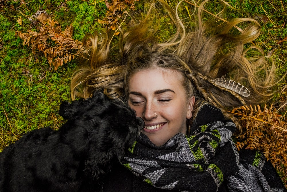 smiling woman lying on ground beside black dog at daytime