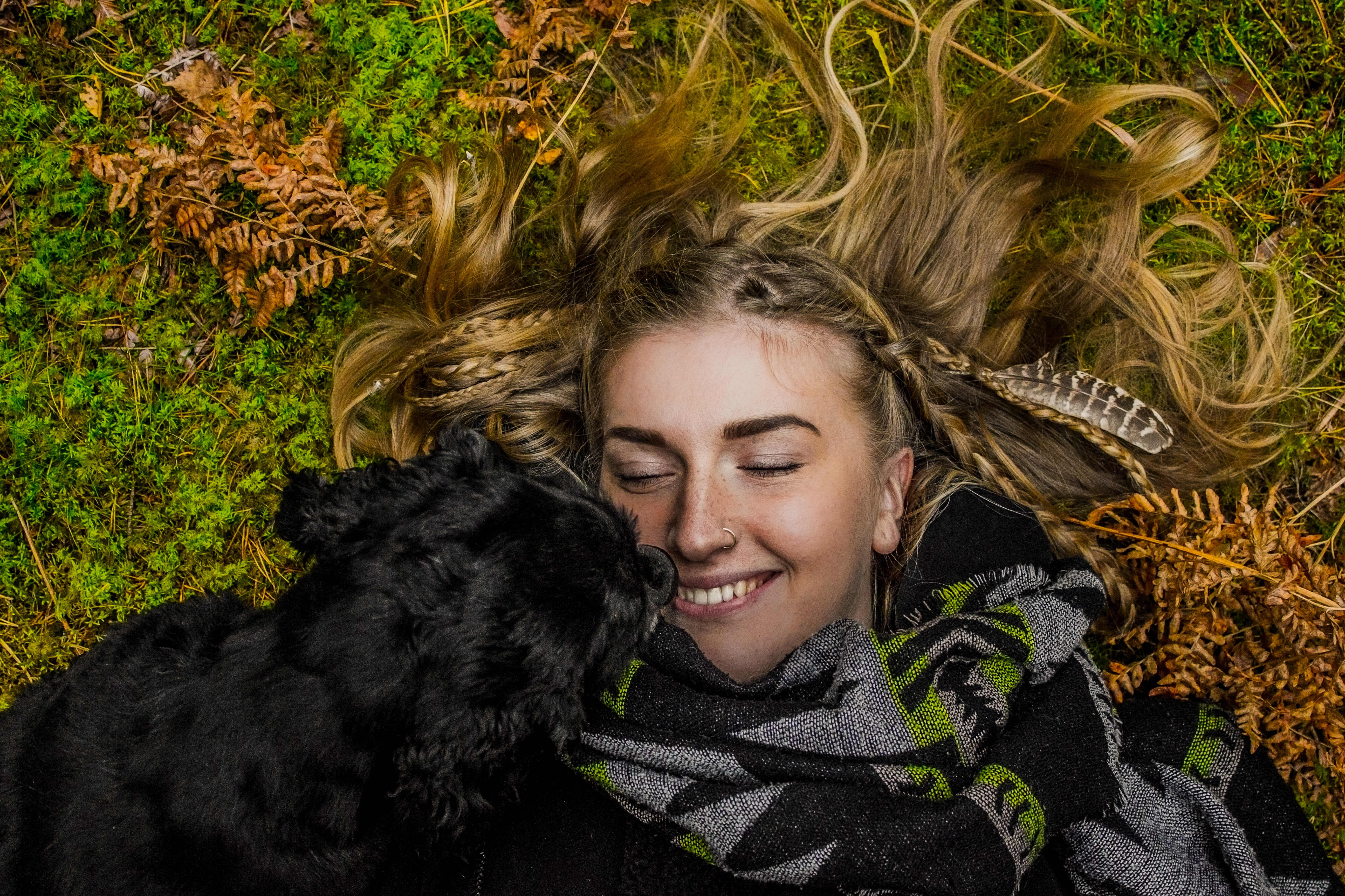 A black dog snuggling up to a smiling woman lying on grass