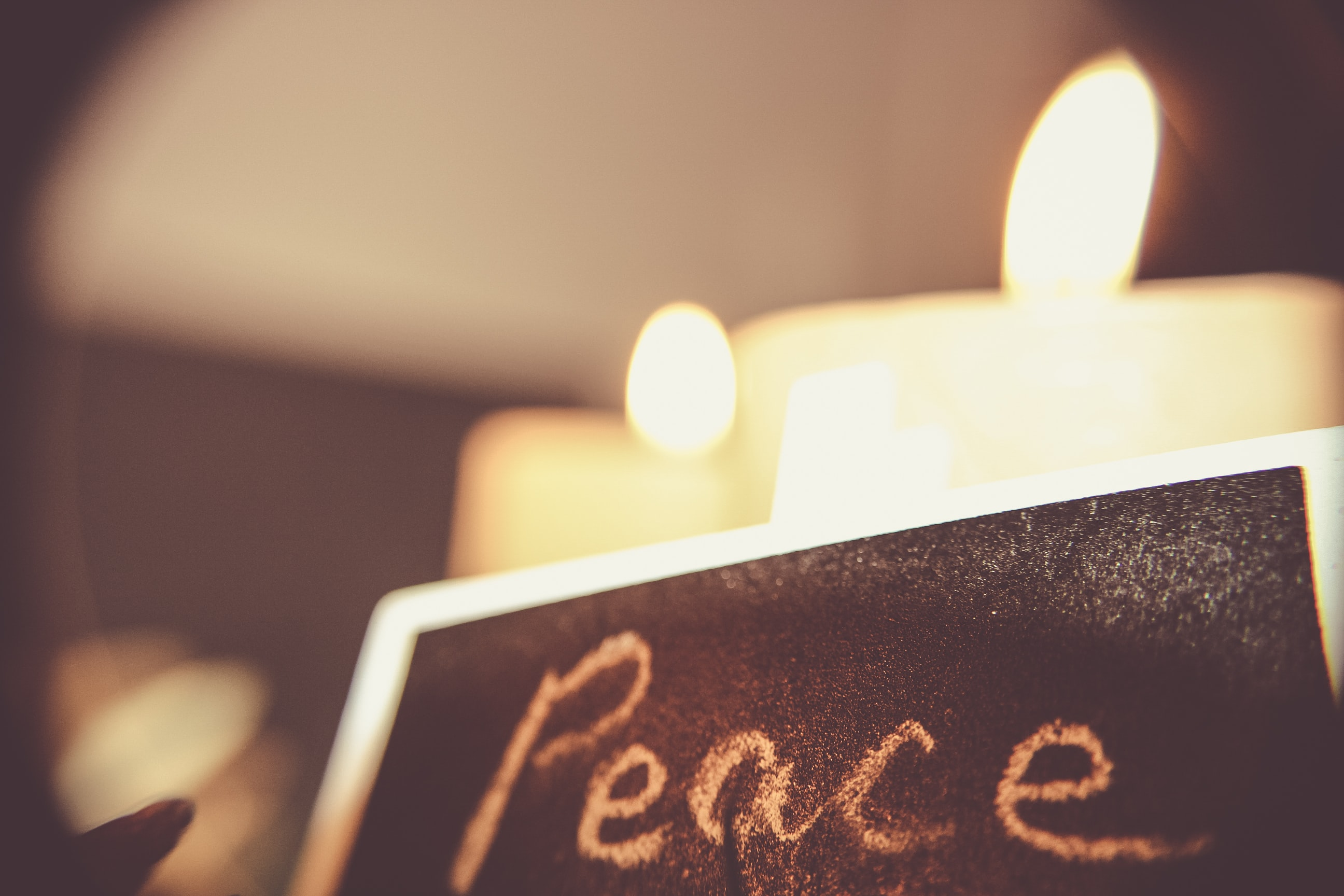 Peace, written on a black chalkboard with white chalk in front of candles.