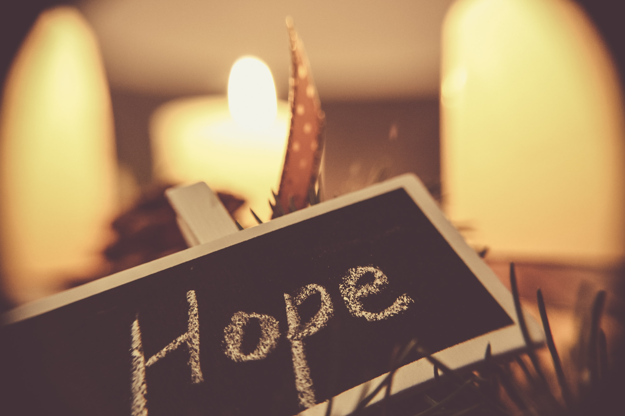 Hope, written in white chalk on a black chalkboard in front of candles.