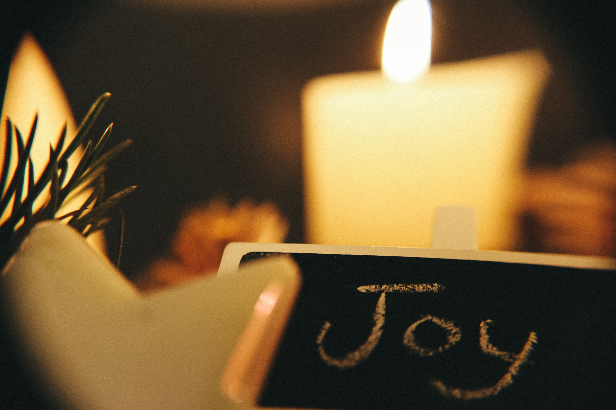 "A black chalkboard that says ""Joy,"" in white chalk, with white candles in the background."