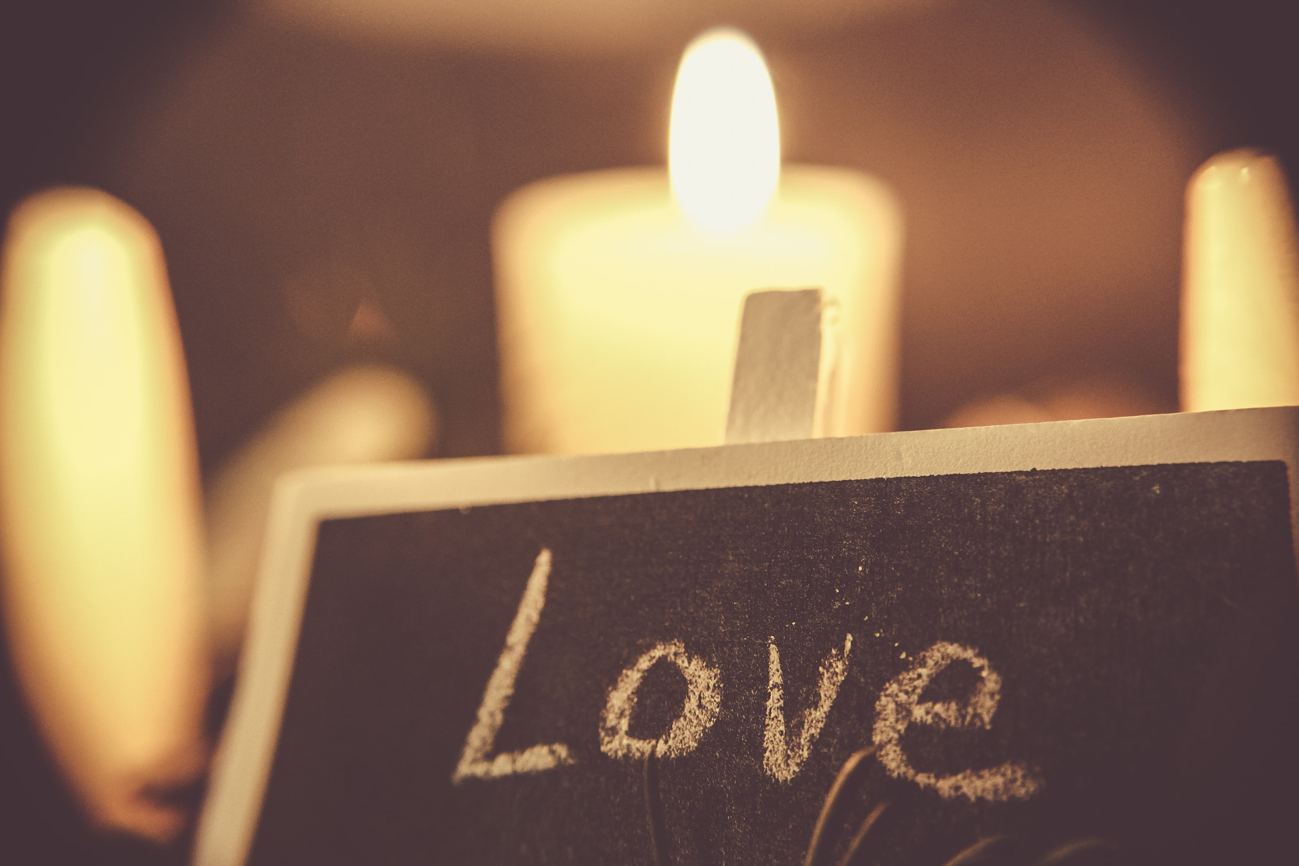 "A black chalkboard that says ""Love,"" with white candles in the background."