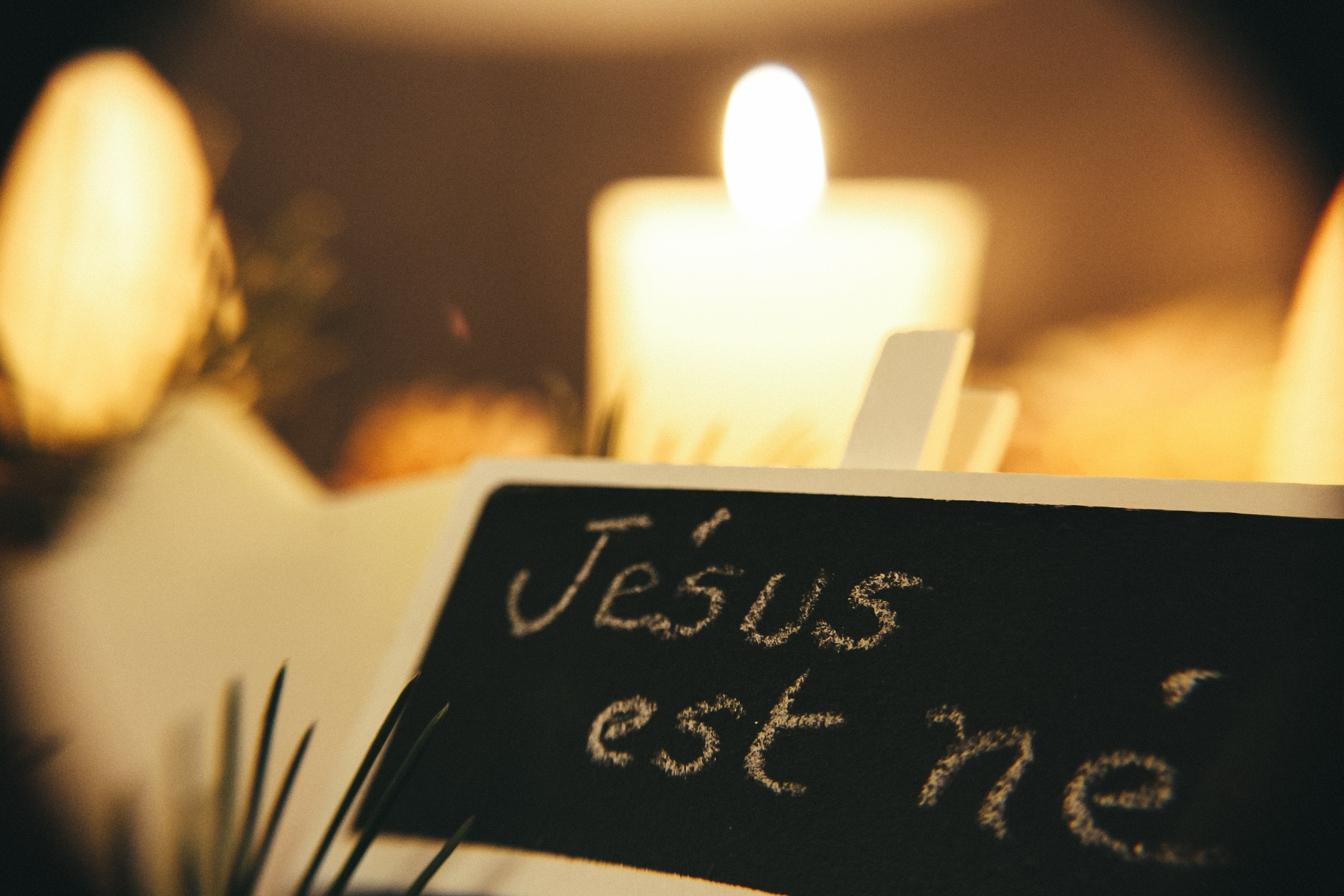 "White chalk writing on a black chalkboard that reads ""Jesus est ne,"" in front of a lit candle."