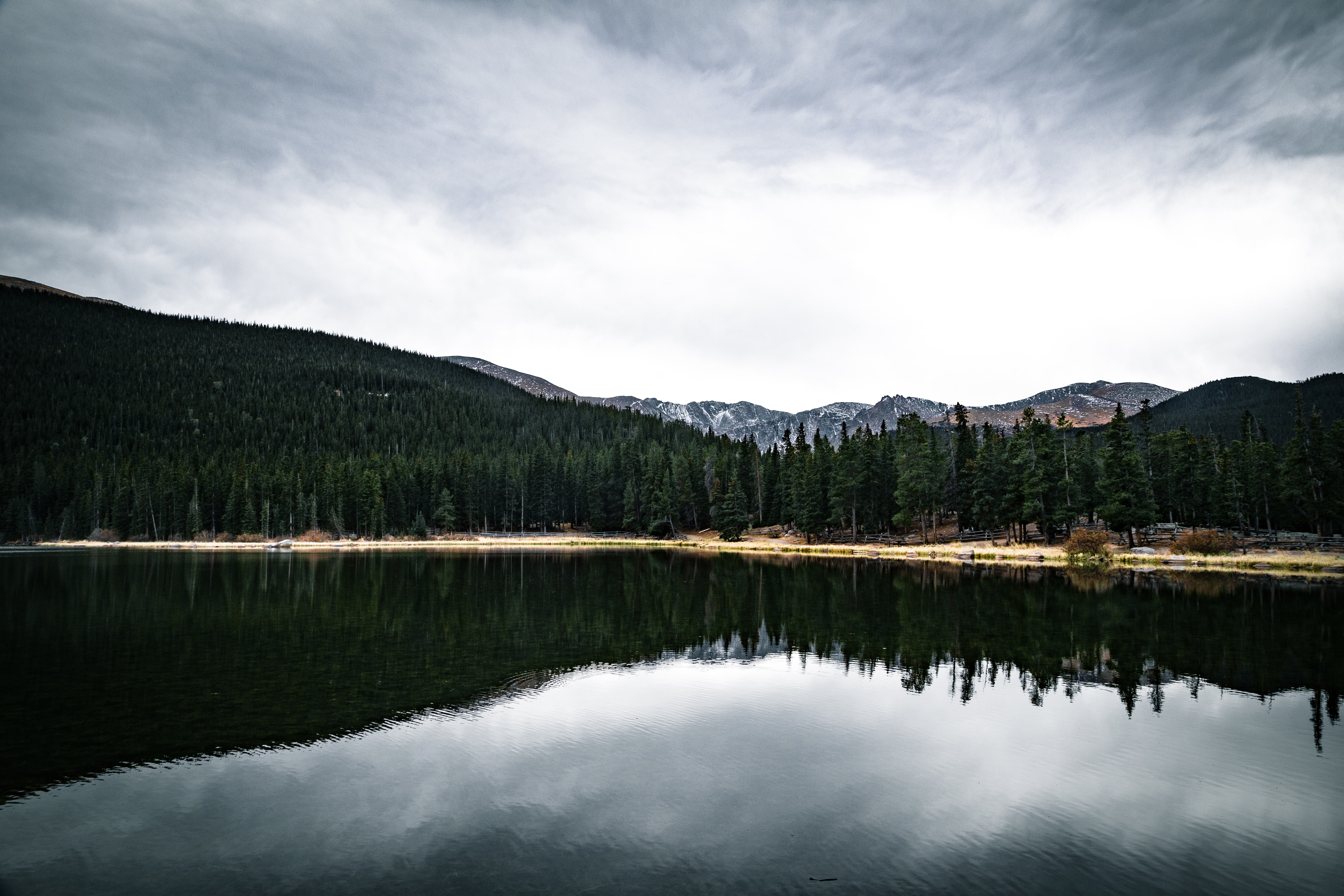 body of water beside trees and mountain with cloudy sky