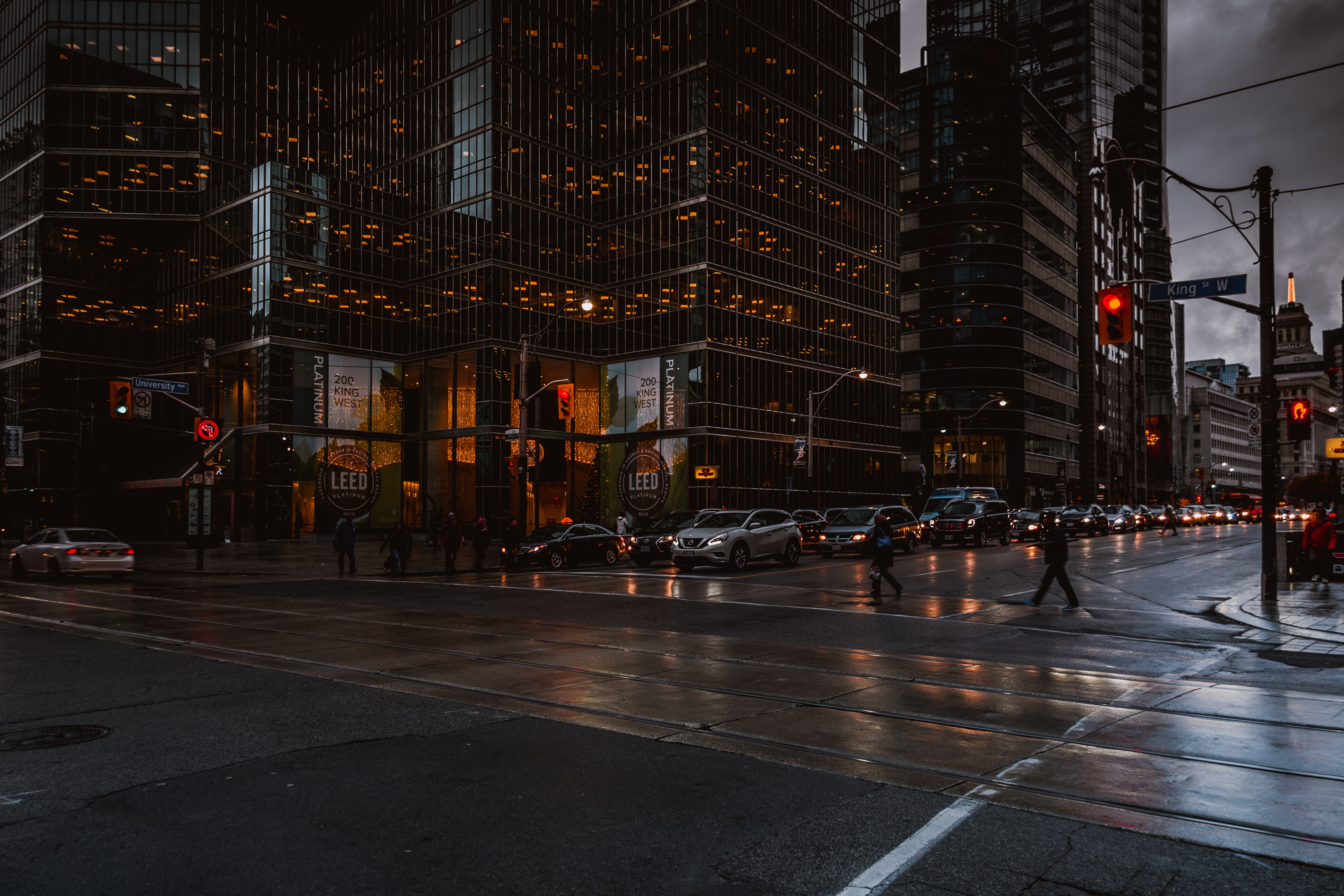 Silhouettes of pedestrians crossing a wet street in Toronto