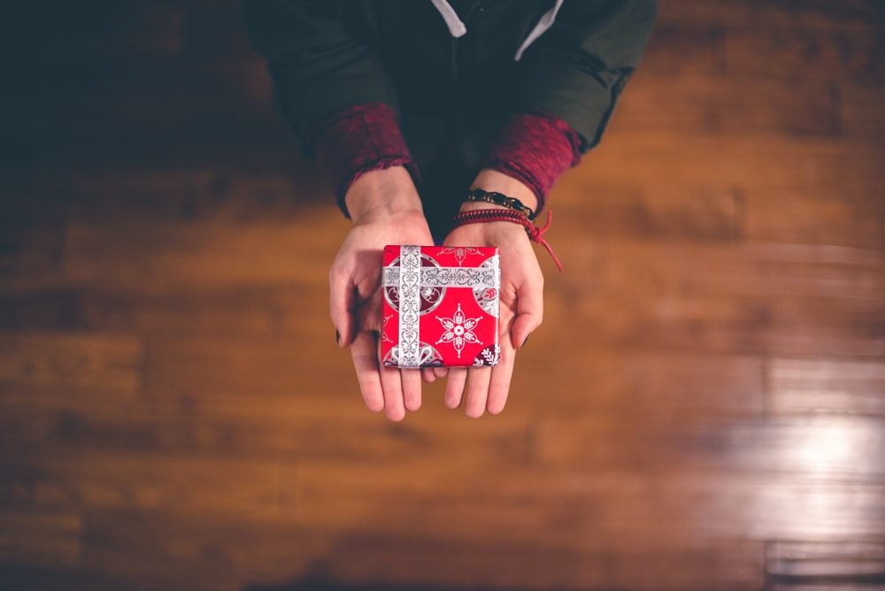 Photo Via: https://unsplash.com/photos/vJz7tkHncFk, Hands outstretched with a Christmas gift wrapped in holiday wrapping paper