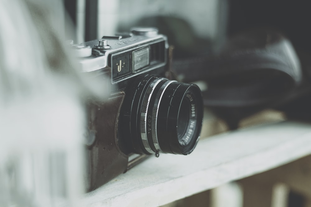 selective focus photography of camera on wooden rack